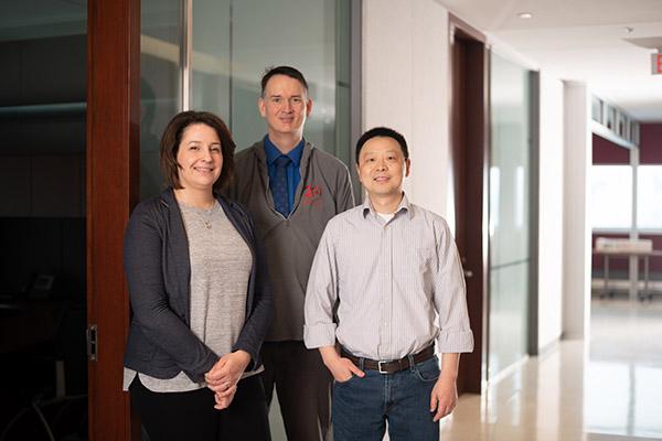 Three team members in a hallway