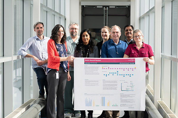Medical research team members hold a progress chart