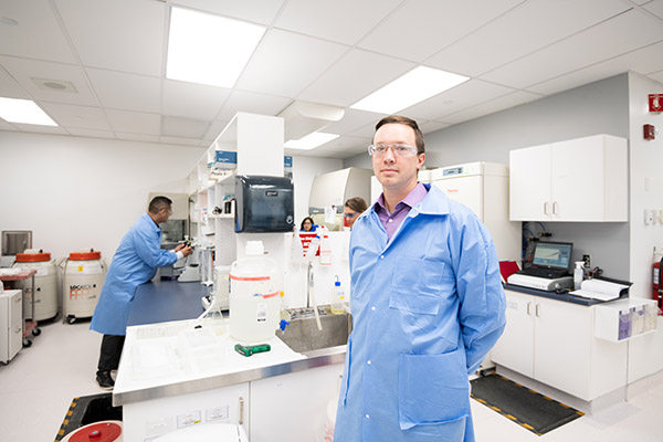 A lab technician posing in the center of the lab.