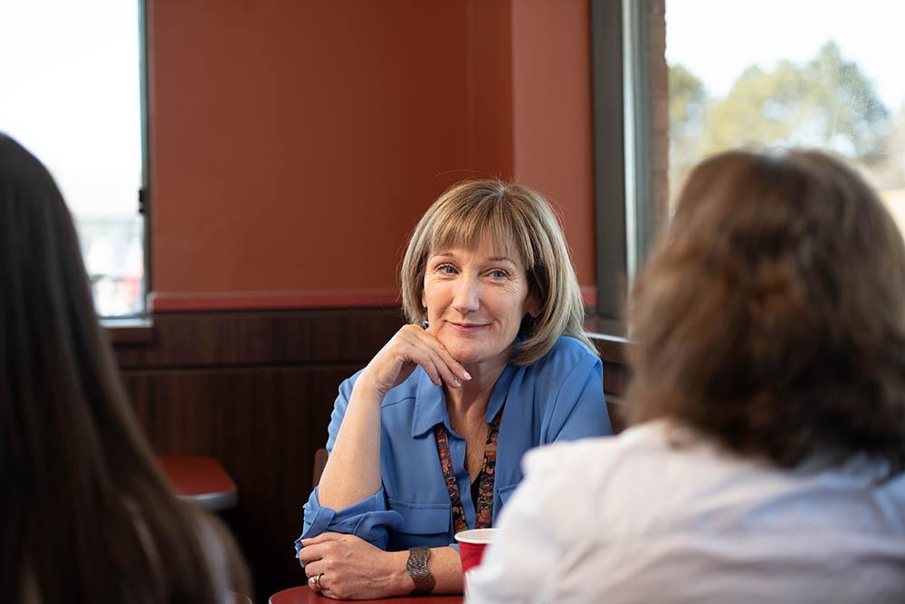 Three people share a conversation of coffee. © Robert Lowdon