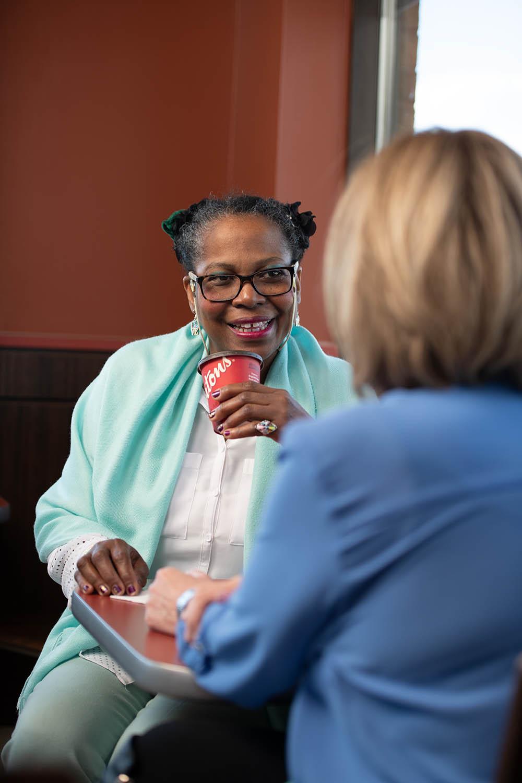 A women drinks coffee over conversation. © Robert Lowdon