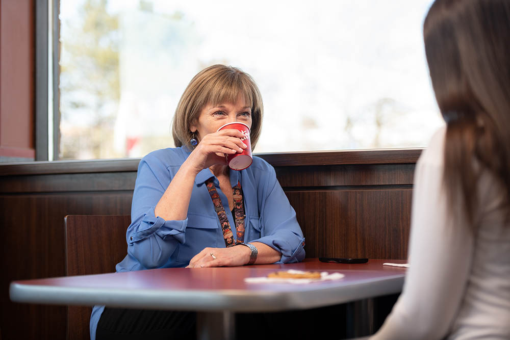 A employee of YSSN drinks coffee with a client. © Robert Lowdon