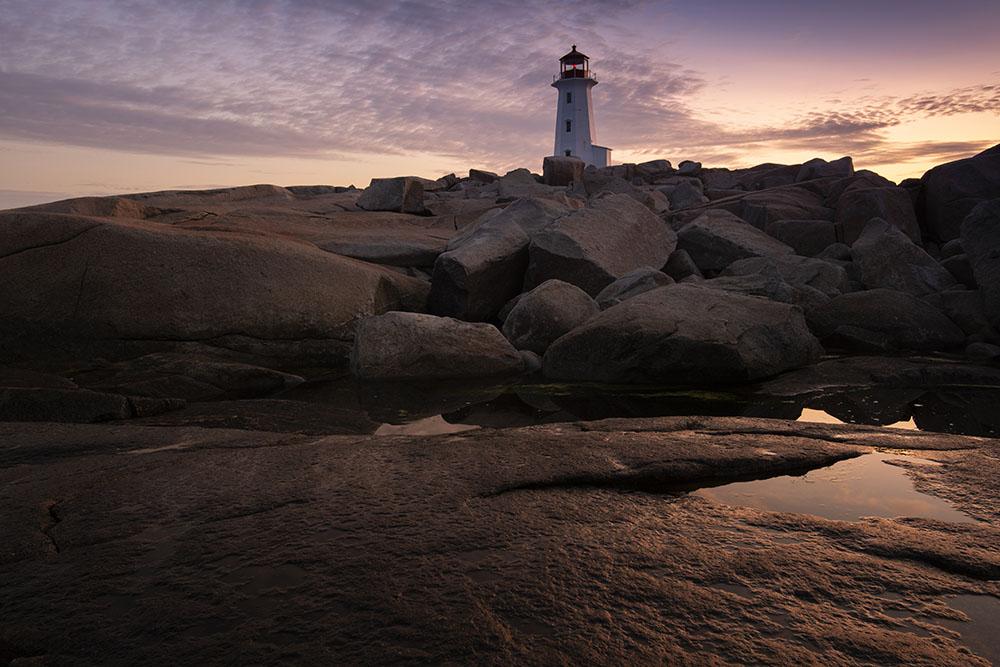 The rocks reflect the rising sun at Peggys Cove. © Robert Lowdon