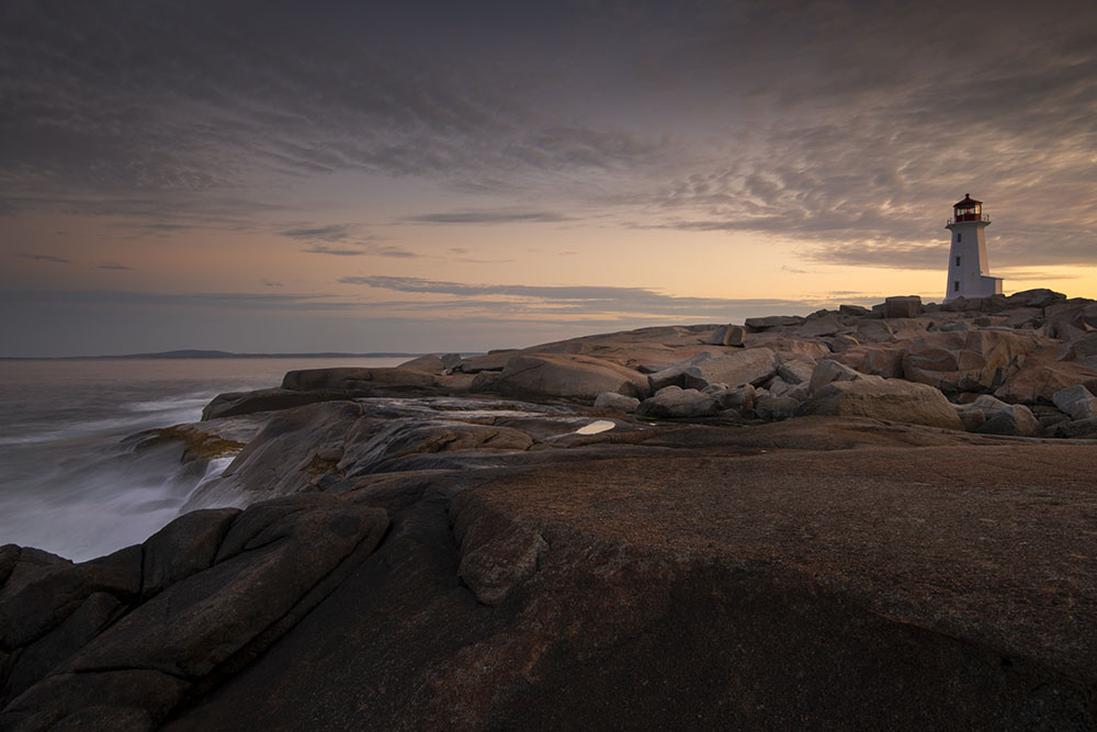 Early morning waves crash into the coast near the lighthouse. © Robert Lowdon