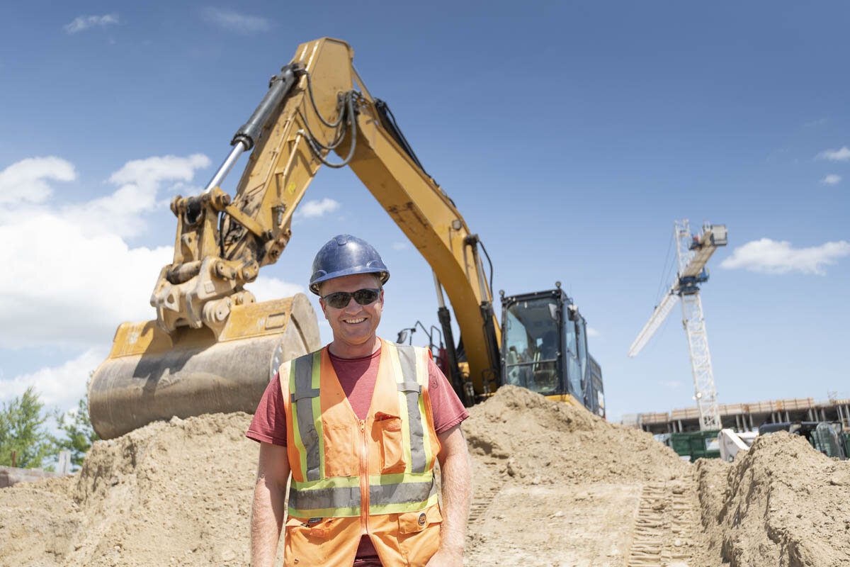 An operator of an excavator in front of his machine. © Robert Lowdon