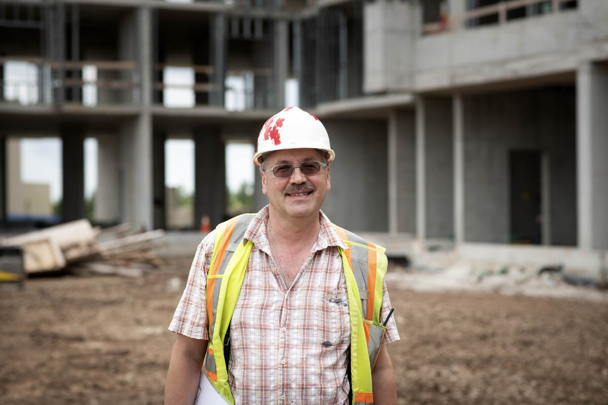 A worker smiles in front of the job site. © Robert Lowdon