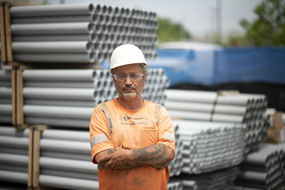 A construction worker in front of various job materials. © Robert Lowdon