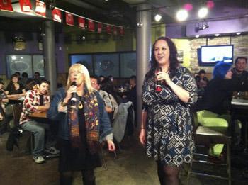 Brandon University President Dr. Deborah Poff, and BUSU President Carissa Taylor take part in karaoke at SUDS during Snowientation. (Jenna Clinton / BUSU)