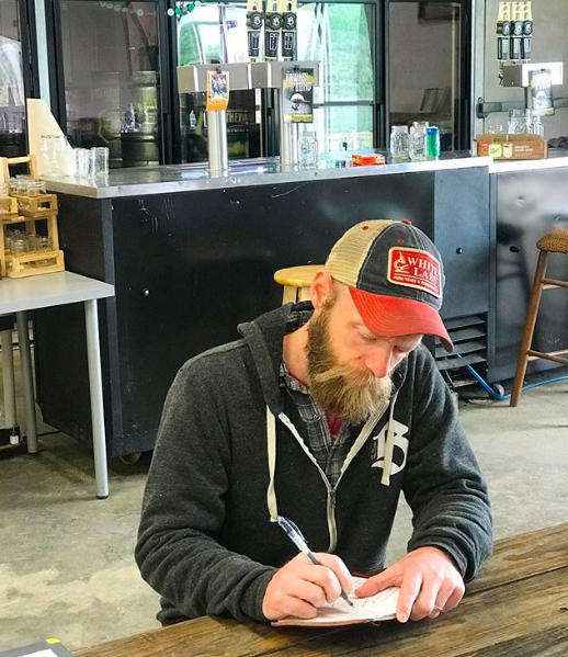 Jacob Martinka, head brewer of Brotherwell Brewing, takes notes before a busy day of production.