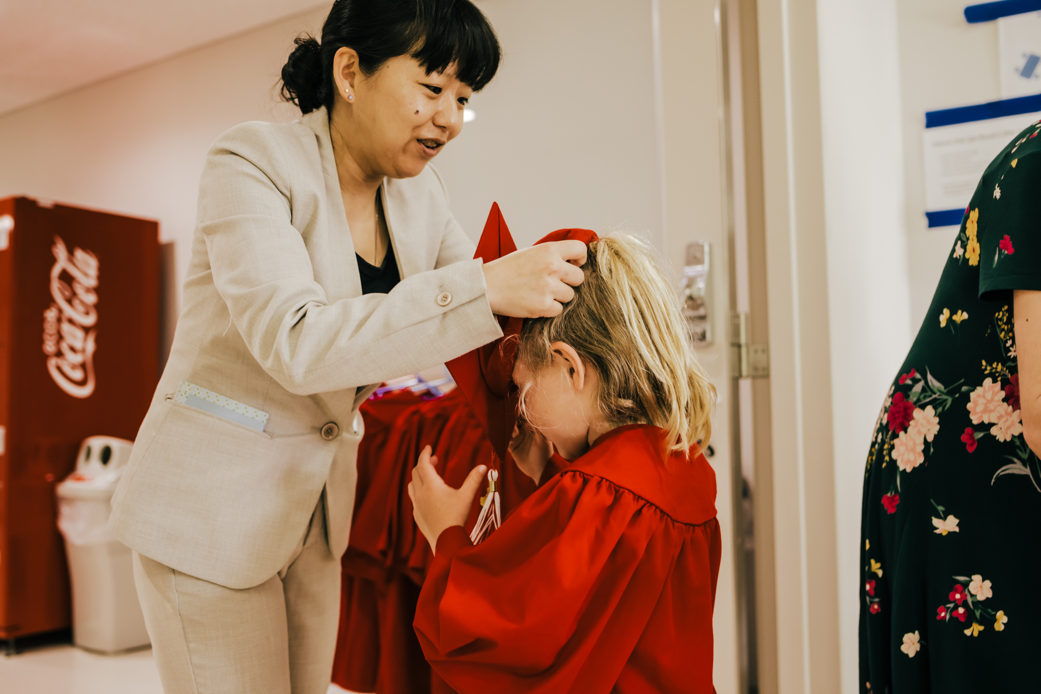 Abigail's sweet teacher helping her get dress in her cap and gown