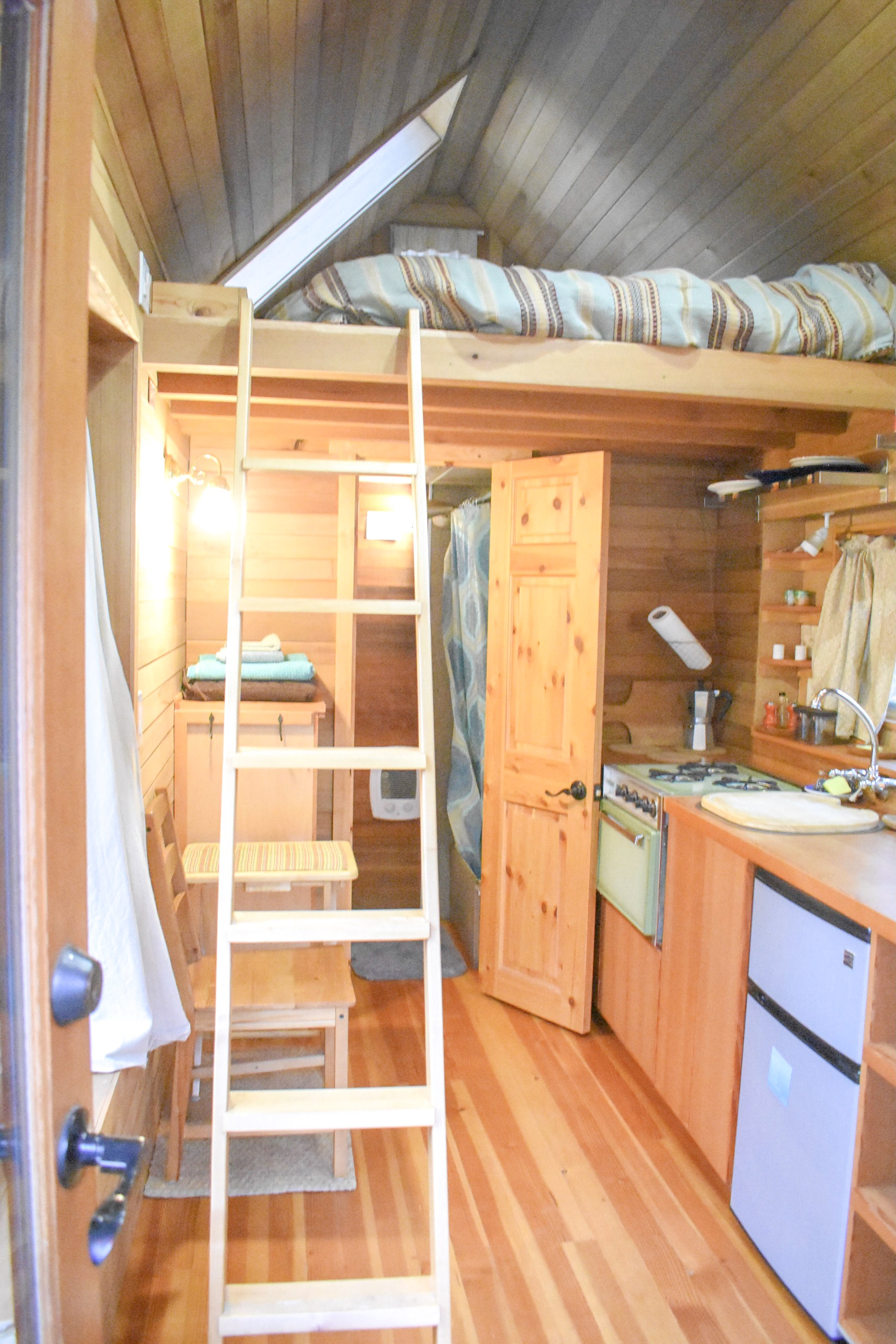Just inside: A ladder leading up to the loft bed, a minimalist kitchen, and a bathroom.