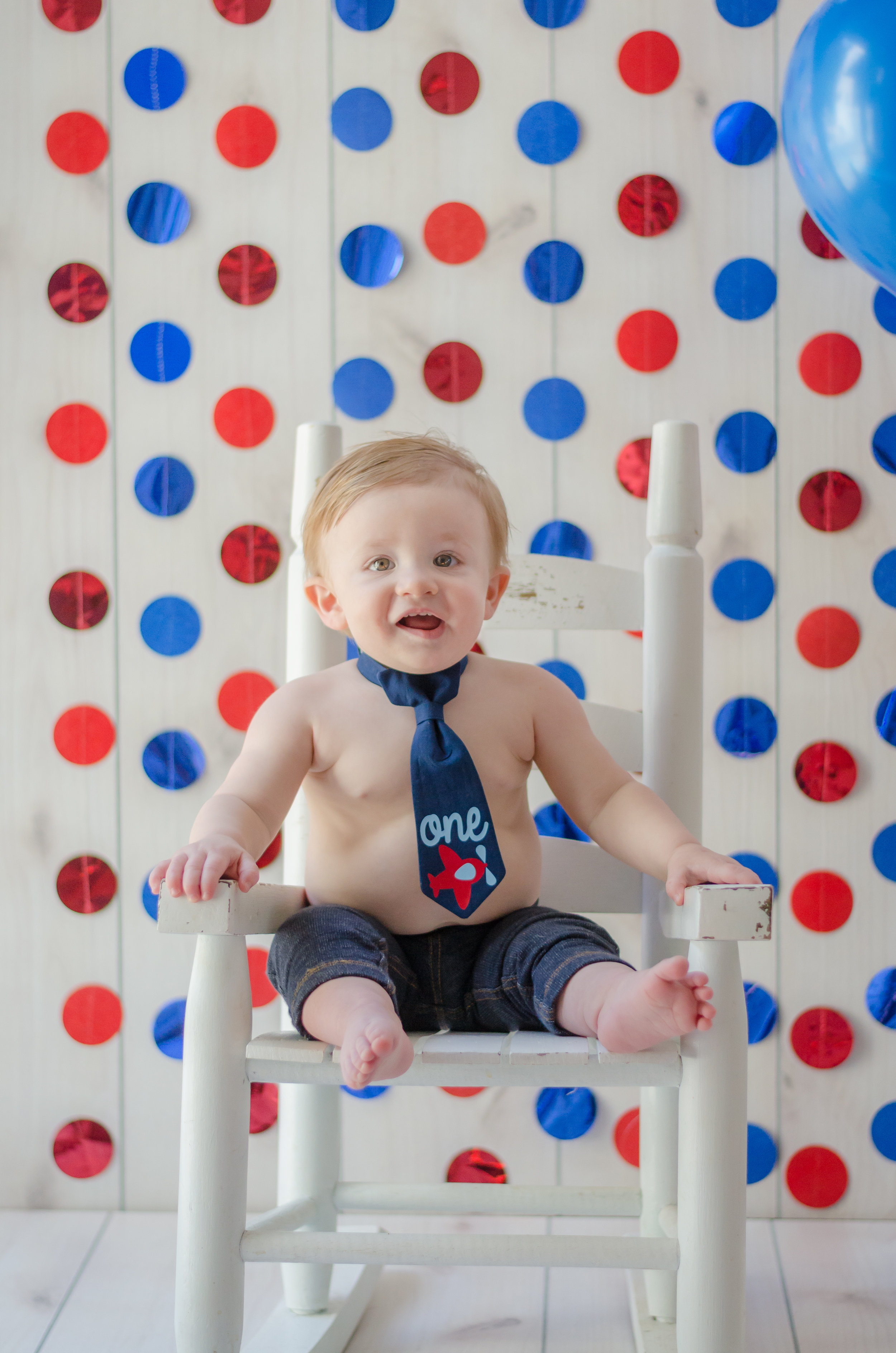 Adorable baby boy wearing a tie sitting in a rocking chair for his first birthday with balloons