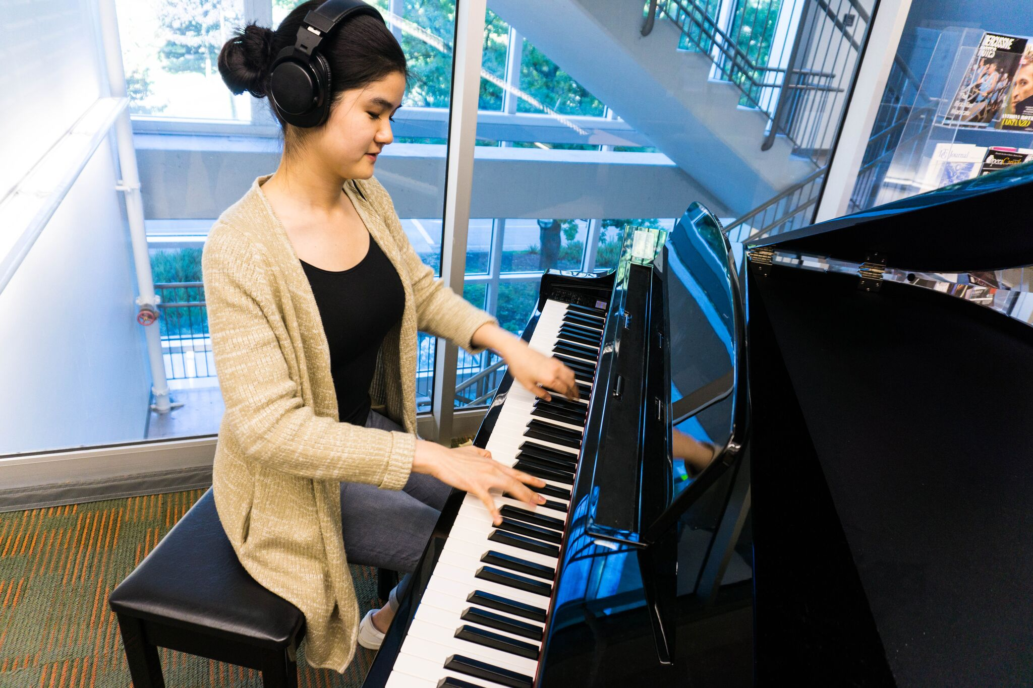 BMus student Serina Mui plays the new piano in the Music, Art and Architecture Library. The instrument is a gift from Tom Lee Music. Credit: UBC Library Communications