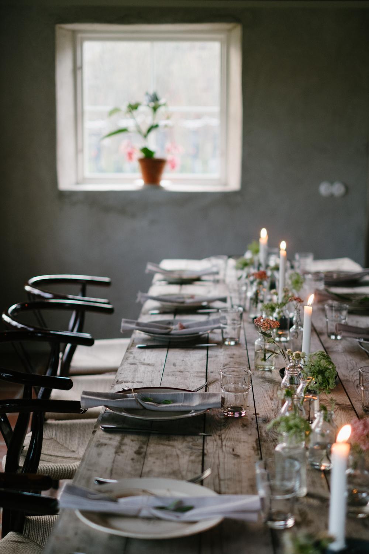 Vi bar in och dukade upp ett härligt långbord. Många ljus och små blomvaser med blommor, tygservetter och snöre.