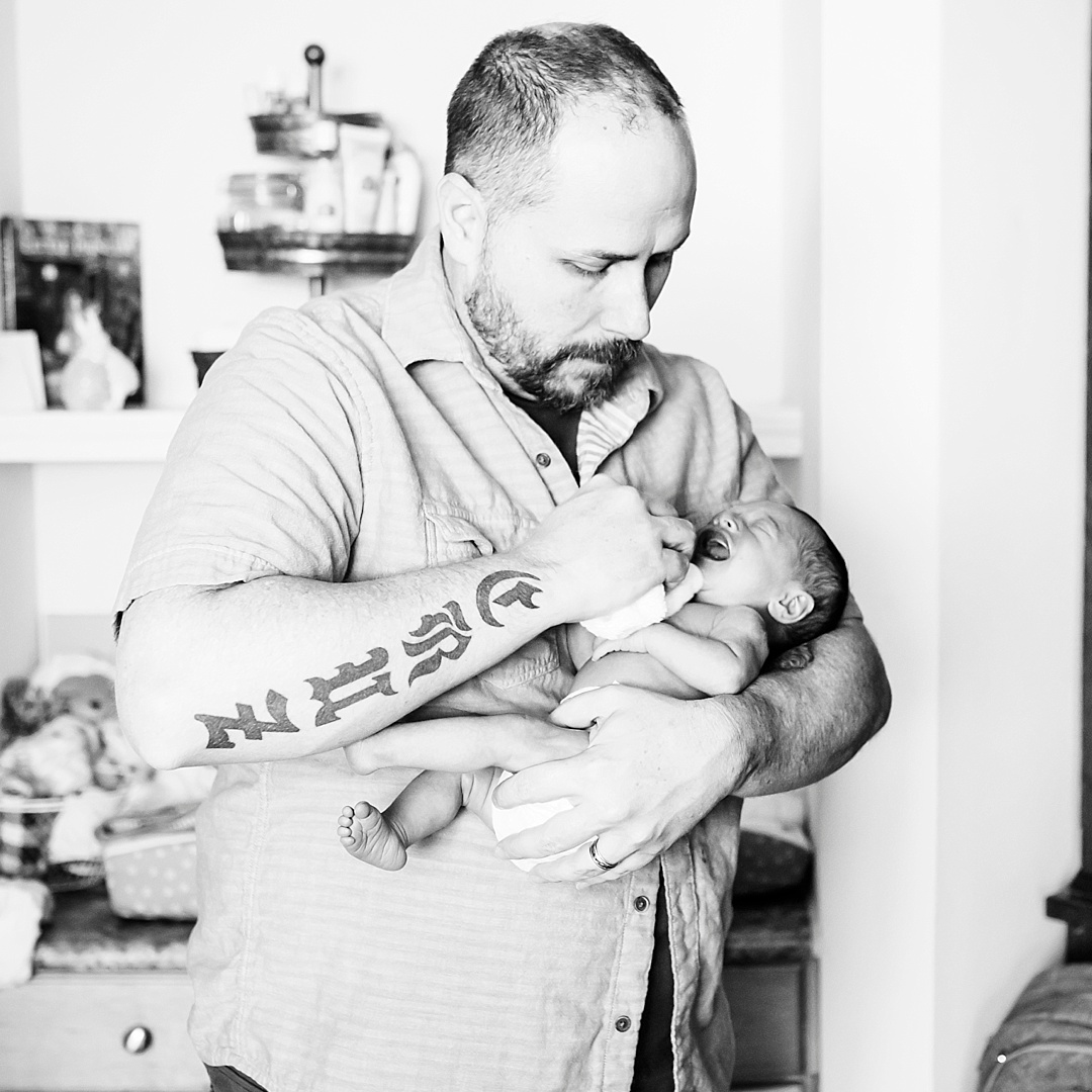 A tatooed father calms his newborn daughter down in Denver, CO   Candid Family Photographer