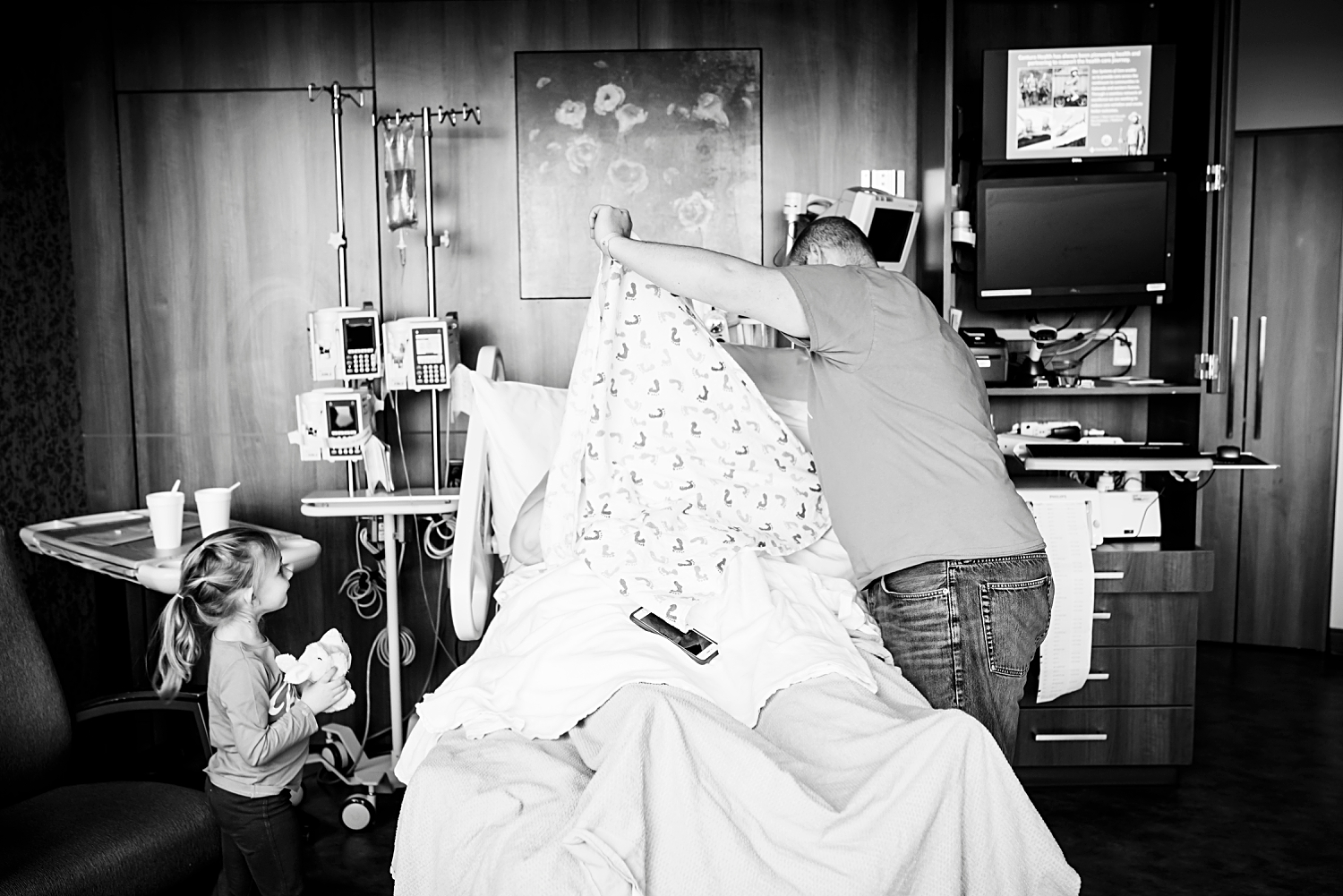 A black and white photo of a family in the hospital room after their son was born during a Fresh 48 in Denver, Co.  Photo by Kristiina Craven Photography.