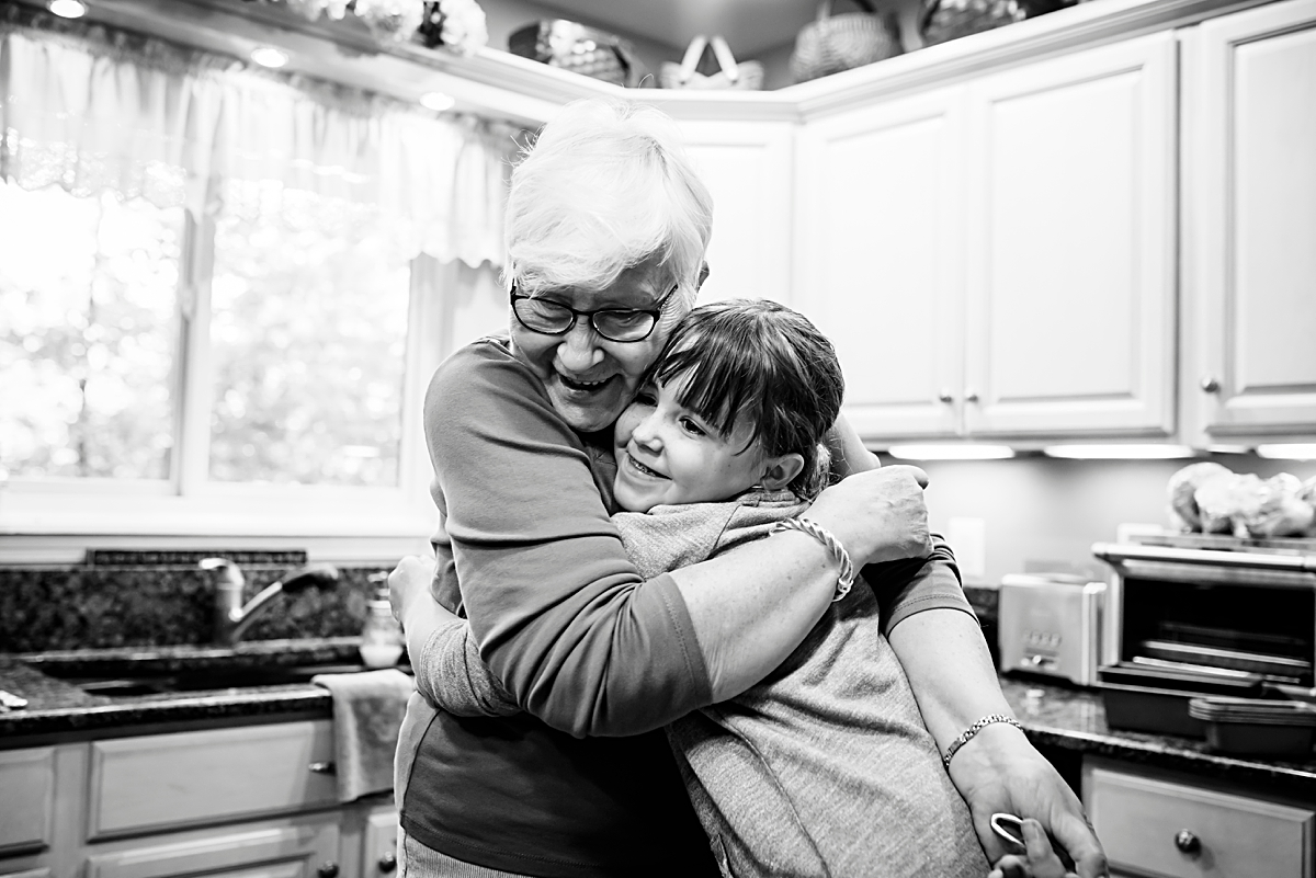 A grandma and her granddaughter hug after baking together--candid shots that show true connections are the best! Photo by Denver Family Photographer, Kristiina Craven.