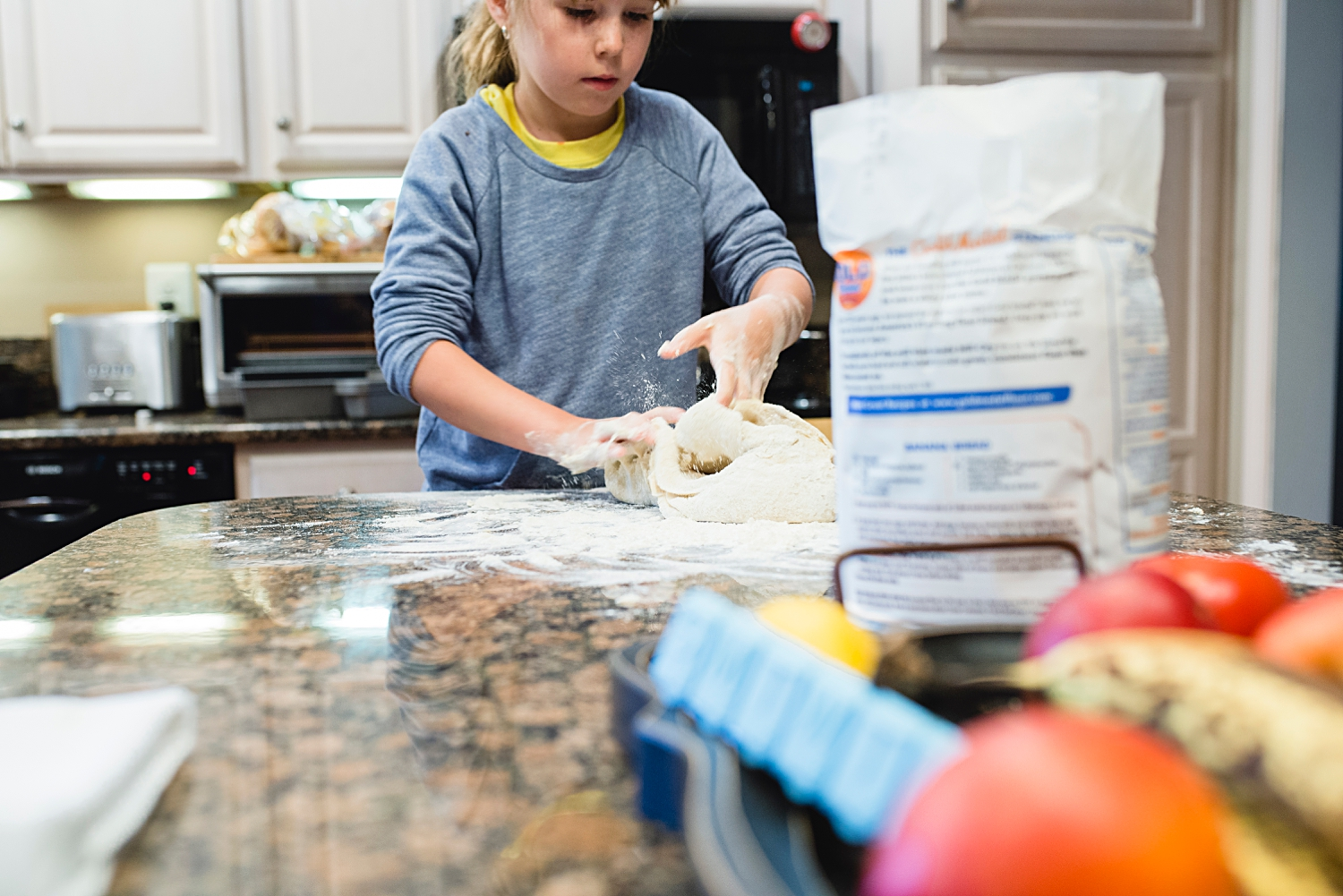A girl kneads her first batch of Finnish pulla bread as shot by Denver Family Photographer, Kristiina Craven.