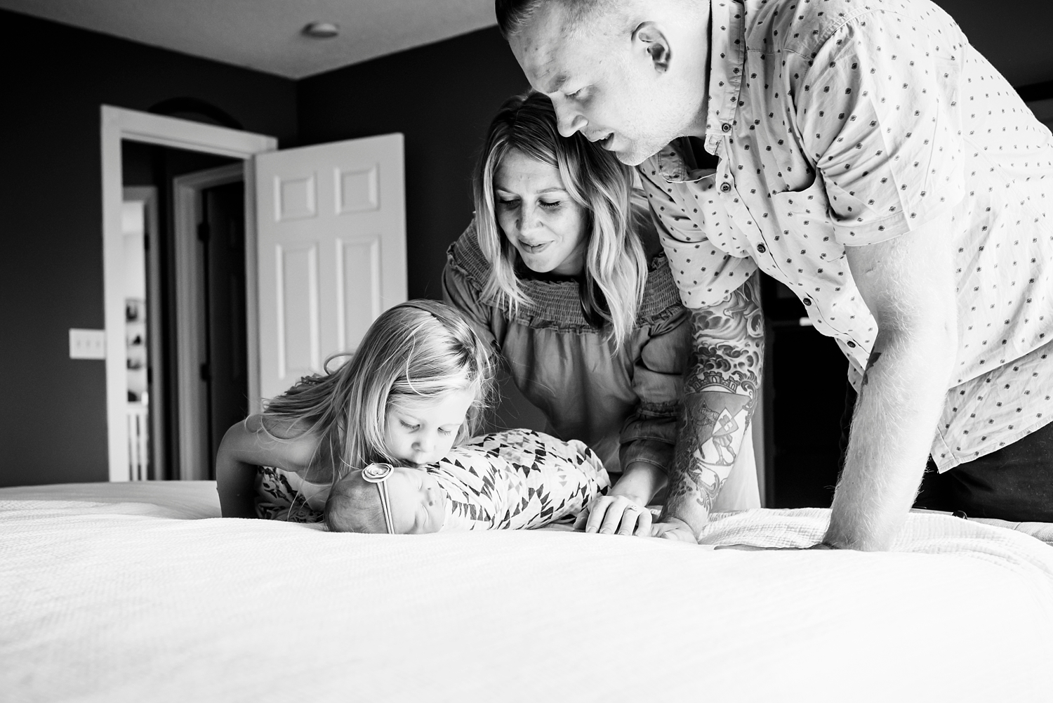 A family gazes down on the newest family addition during a Highlands Ranch Lifestyle Newborn Baby photo session with Kristiina Craven Photography. #denvernewbornphotographer