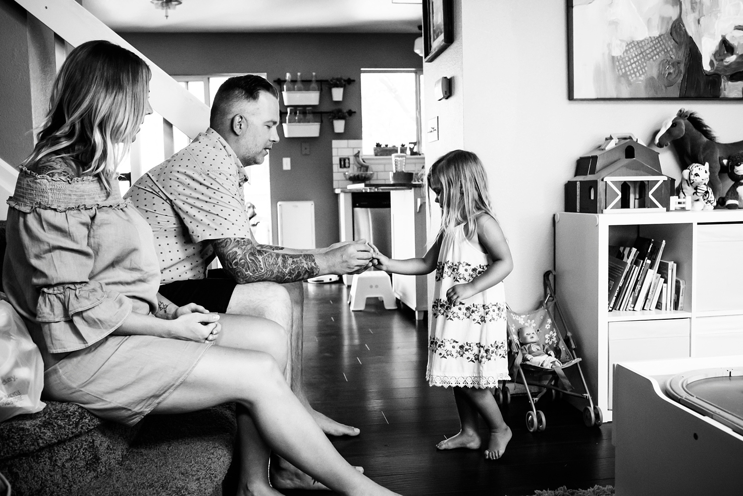 """A little girl serves """"tea"""" to her parents during a lifestyle newborn photo session in Highlands Ranch, Colorado, with Kristiina Craven Photography. #denvernewbornphotos"""
