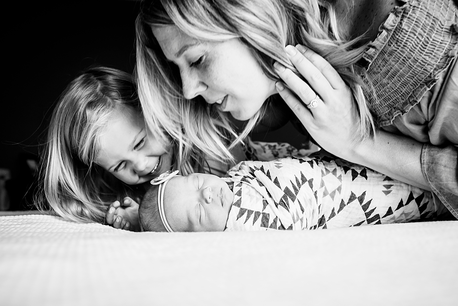 Three girls--a mom and new big sister gaze at a newborn baby girl during a photo shoot in Highlands Ranch, Colorado, with Kristiina Craven Photography.