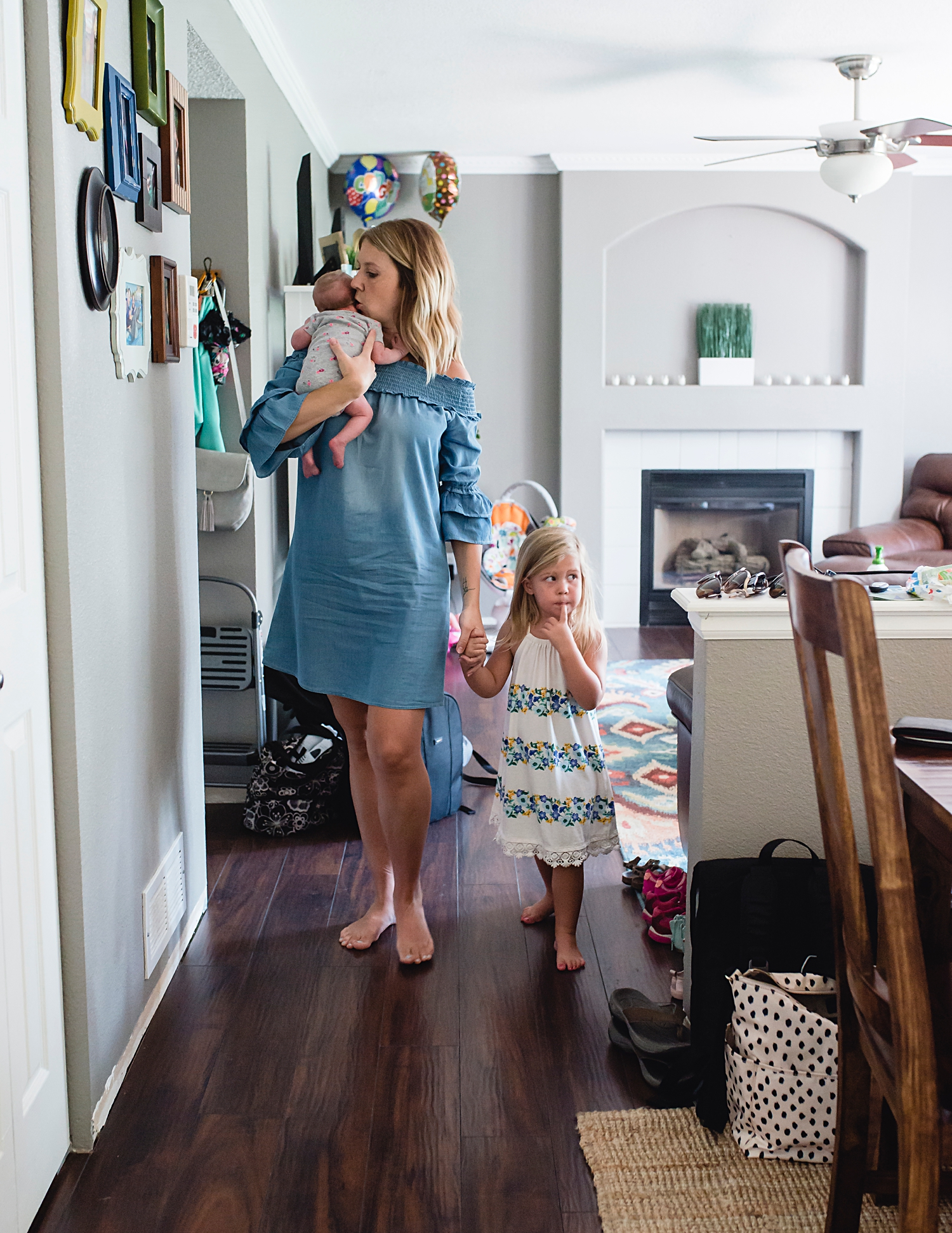 Mom, first born, and newborn baby girl, during a lifestyle newborn photo shoot in Highlands Ranch, Colorado.