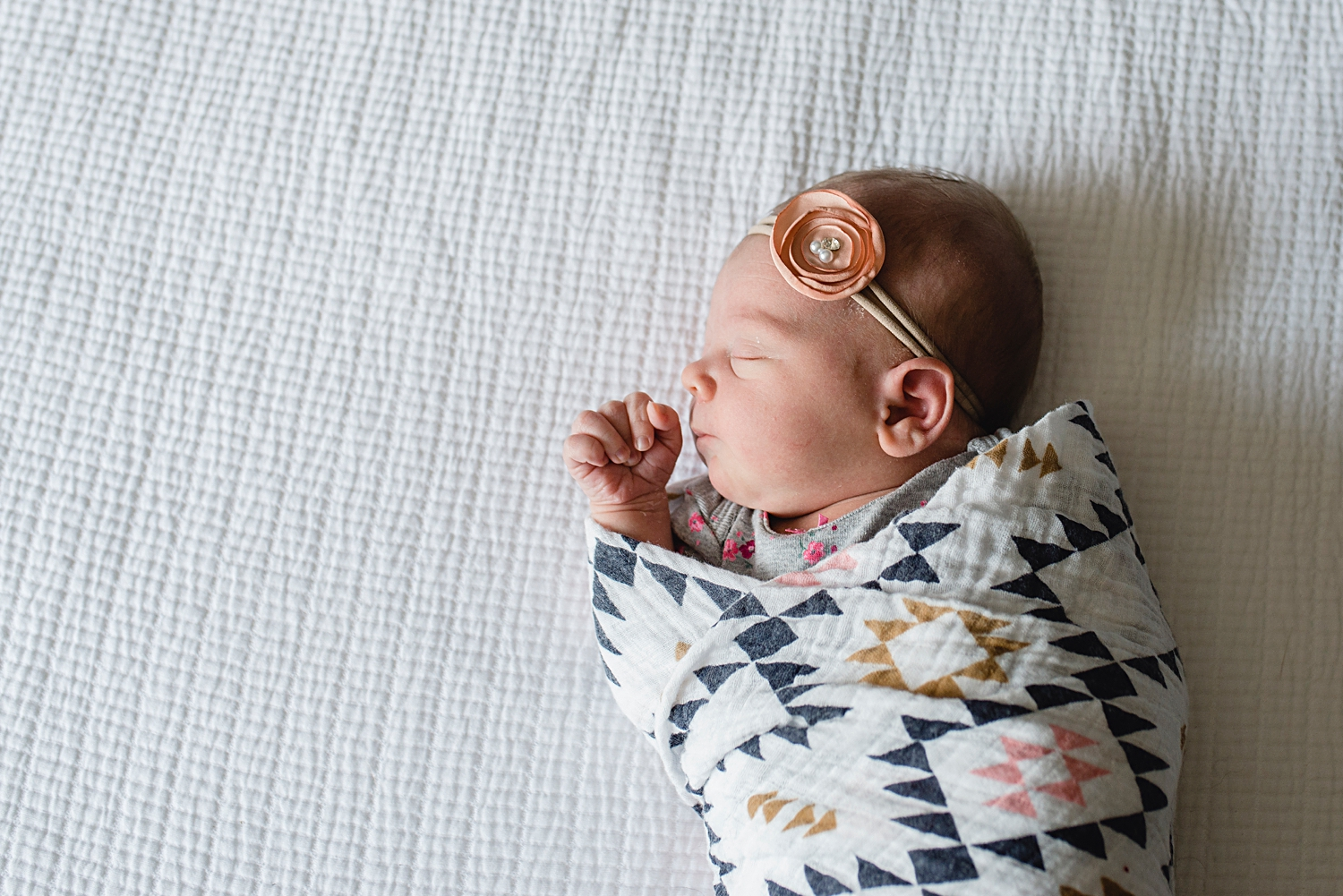 A newborn baby girl in Highlands Ranch, Colorado, is swaddled in an aztec print wrap for her newborn portrait during her first photo shoot.