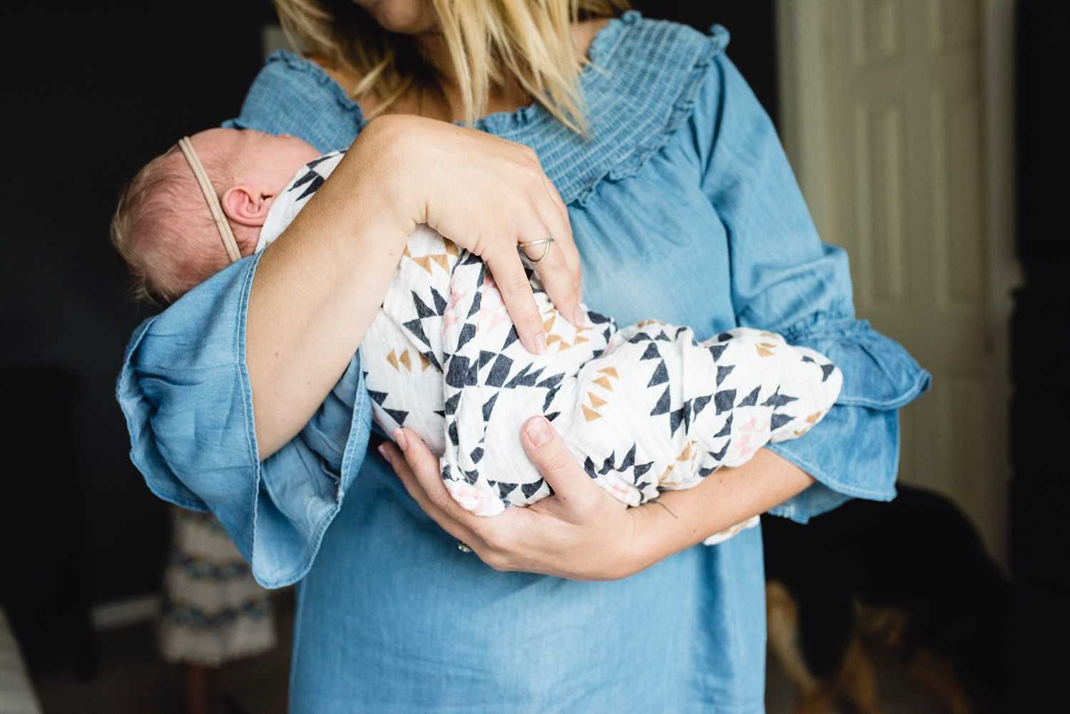A mom holds her newborn baby girl at a lifestyle photo shoot. The photographer reviews what it was like working for Bella Baby Photography.