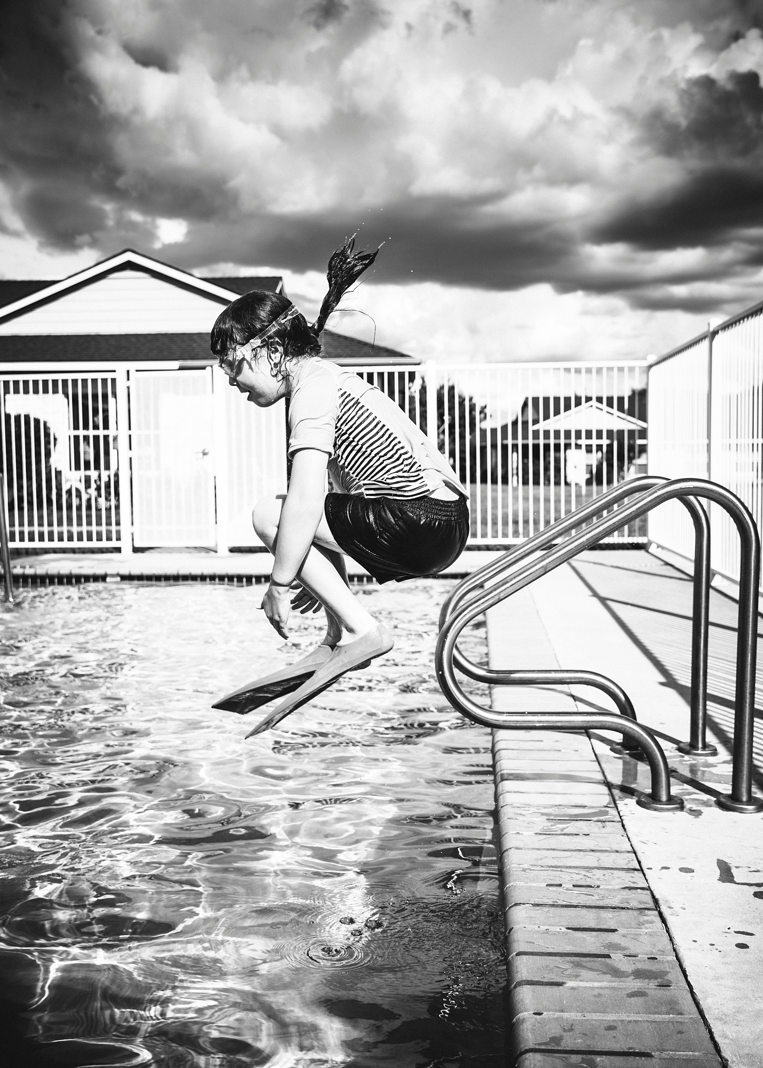 A black and white image of a girl doing a canon ball into the pool in Texas.  Why homeschooling is good :)