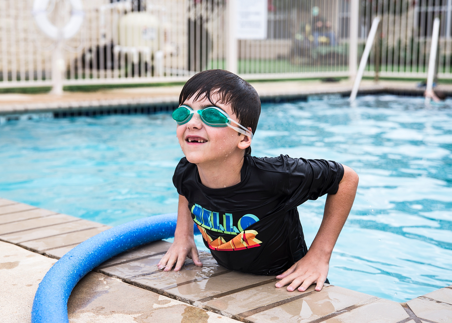 My nephew, missing his front teeth, hops out of the pool in Marble Falls, Tx, in our week in the life of an unschooler series.