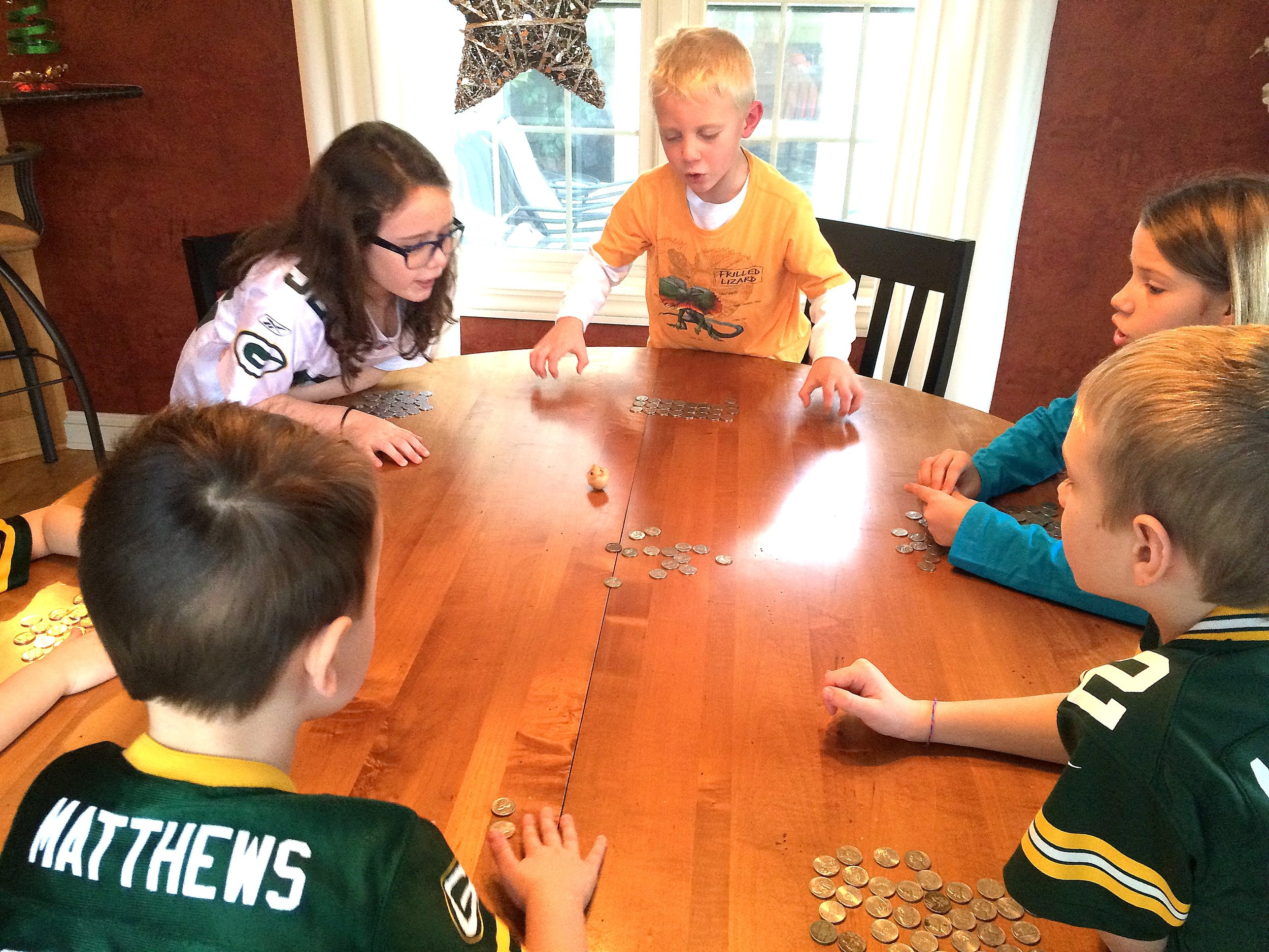 The kids and their cousins playing dreidel.