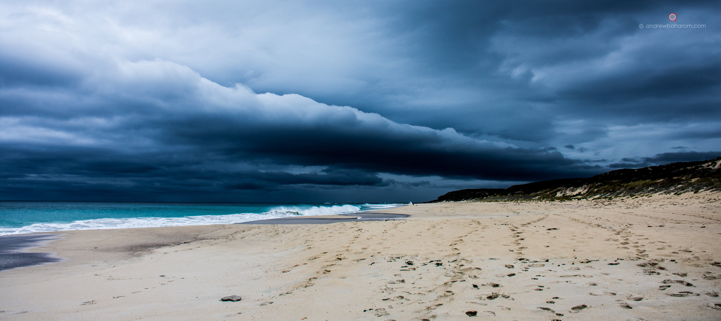Storm clouds rolling in, over a long stretch of beach on the Cape To Cape Track.