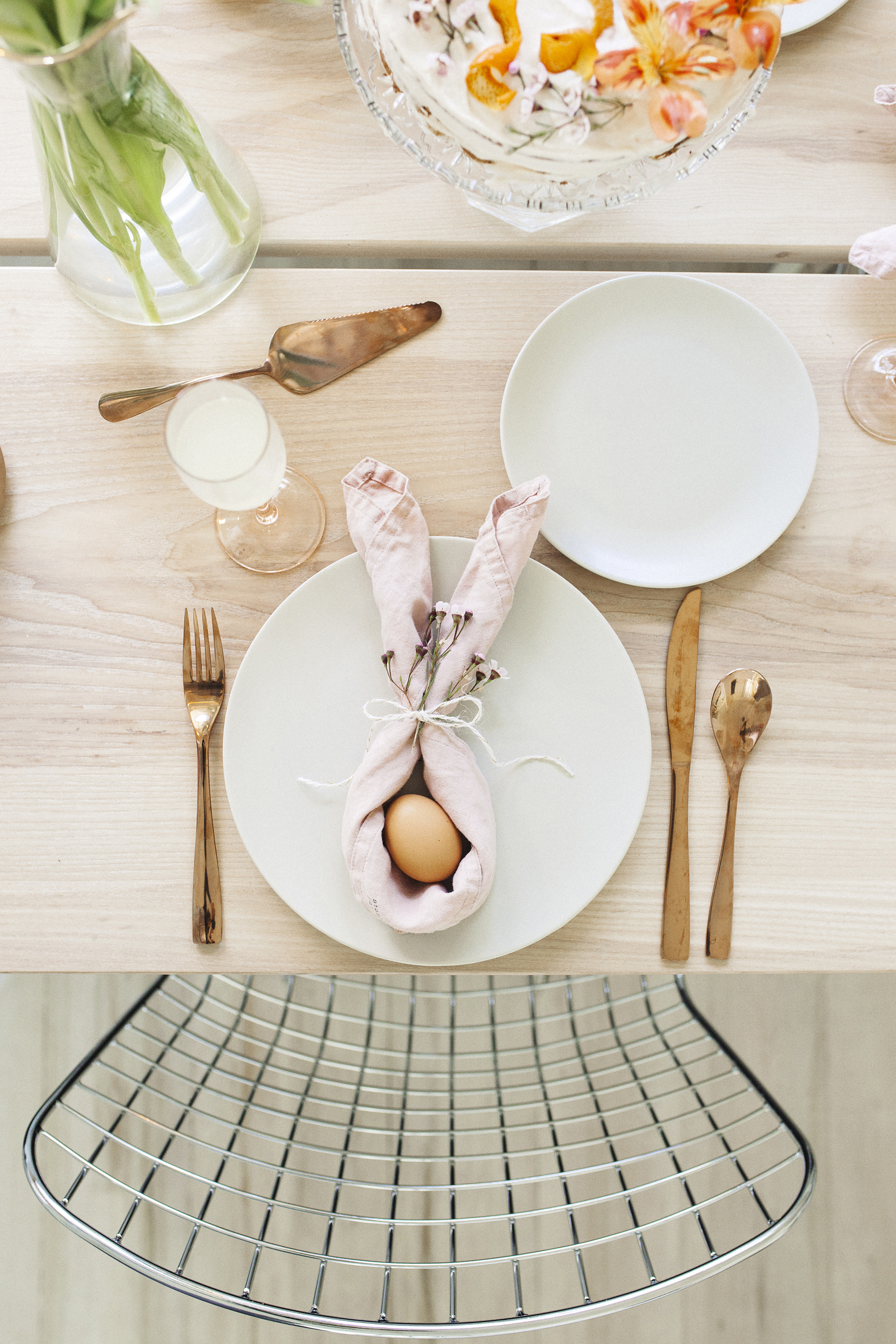 To make these 'bunny' place settings, I rolled linen napkins diagonally lengthwise (as you would with a bandana), folded the ends together and knotted a piece of gold + white baker's twine around the middle. Stick a sprig of spring flowers in the twine and finish with a bow. Place an egg in the middle and voila - you're set for an Easter brunch!