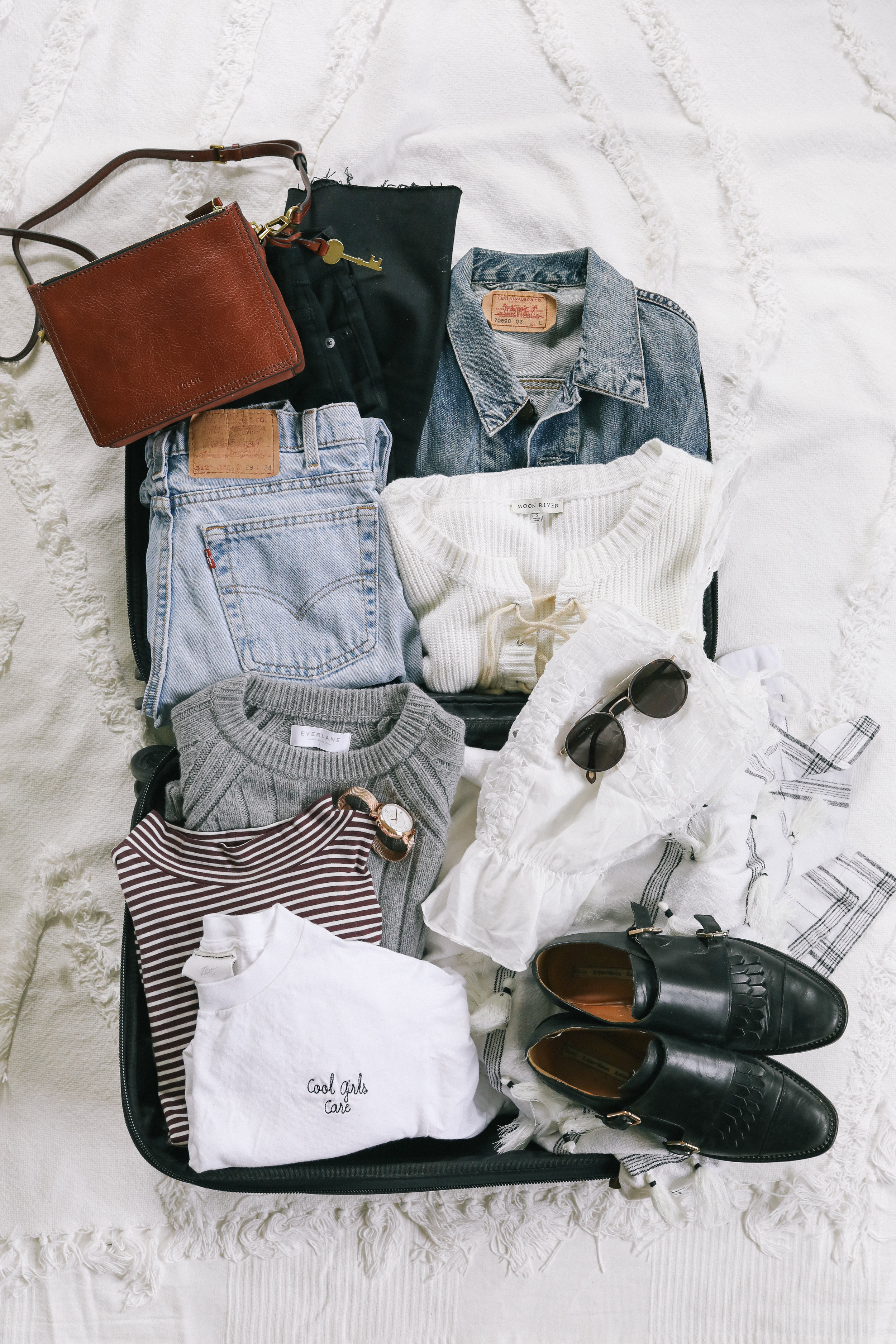 An open suitcase displaying matching outfits and organizational ideas, such as color schemes and white t shirts, to help you pack light