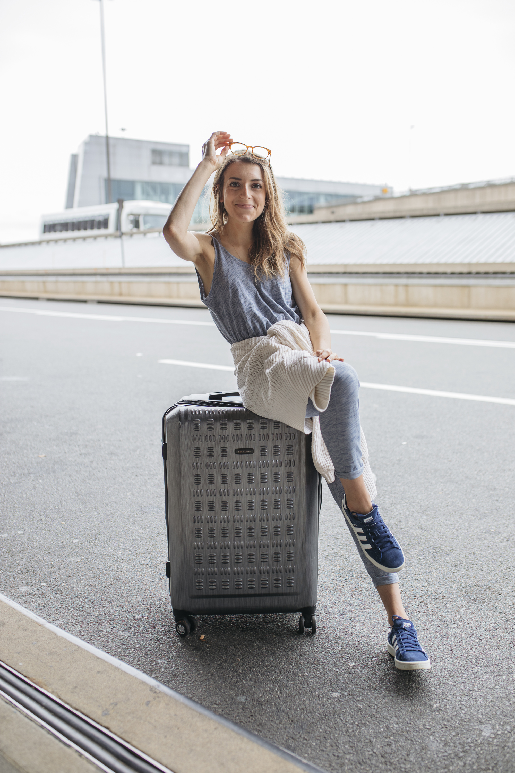 Traveler and blogger poses with suitcase en route to the airport.