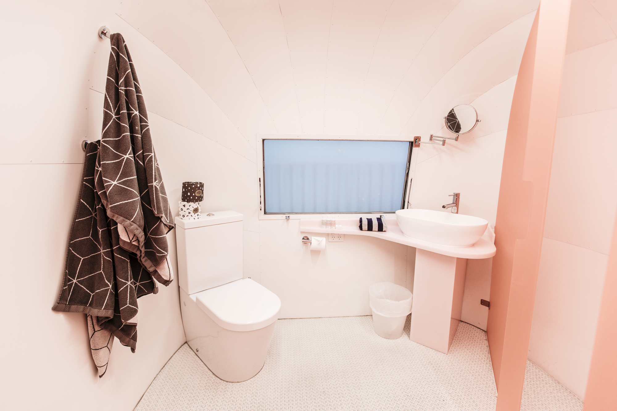 Neon pink bathroom with geo towels gives this hotel a retro vibe.