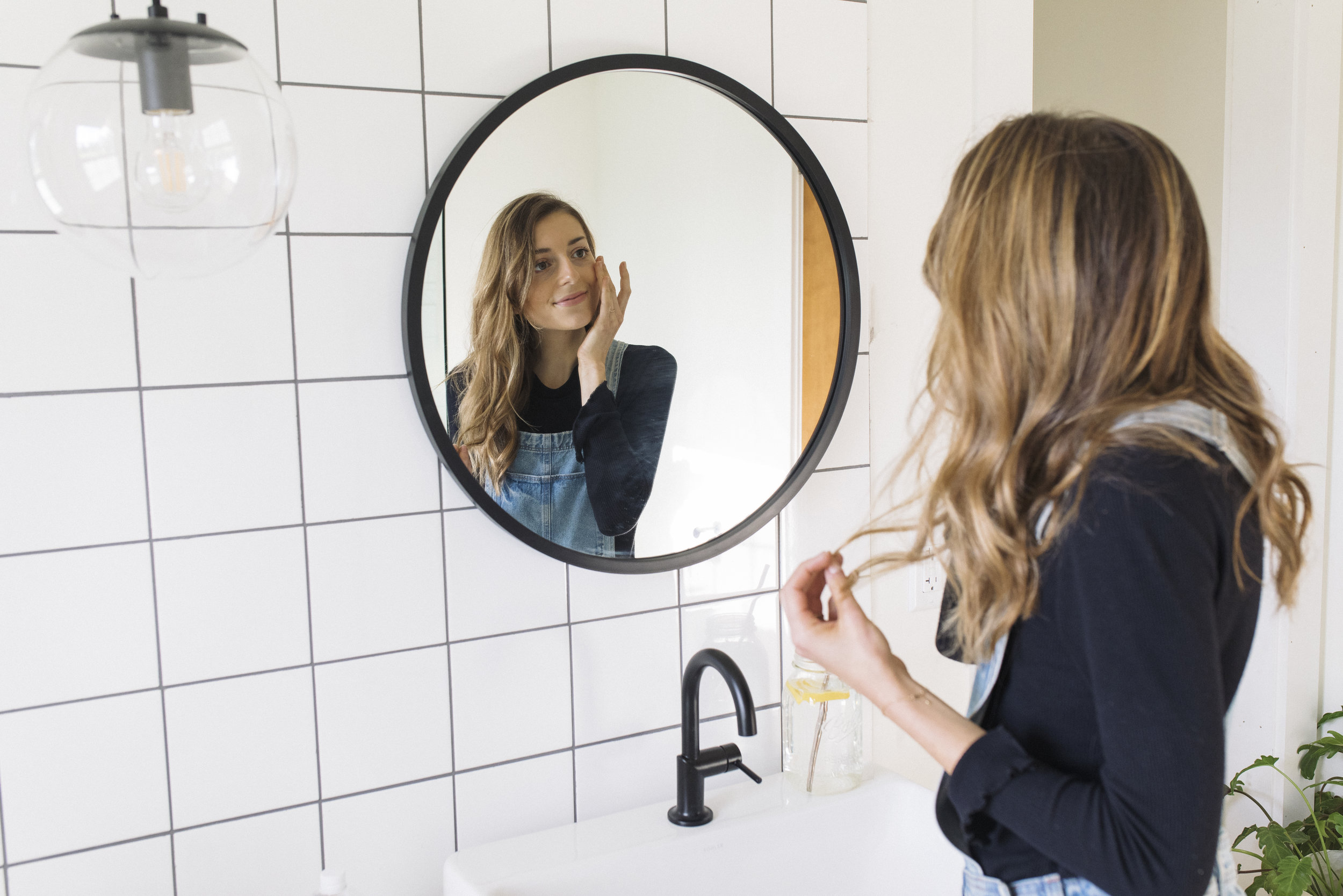 Emily applies face moisturizer in front of mirror to promote healthy skin and a healthy life style of self-love