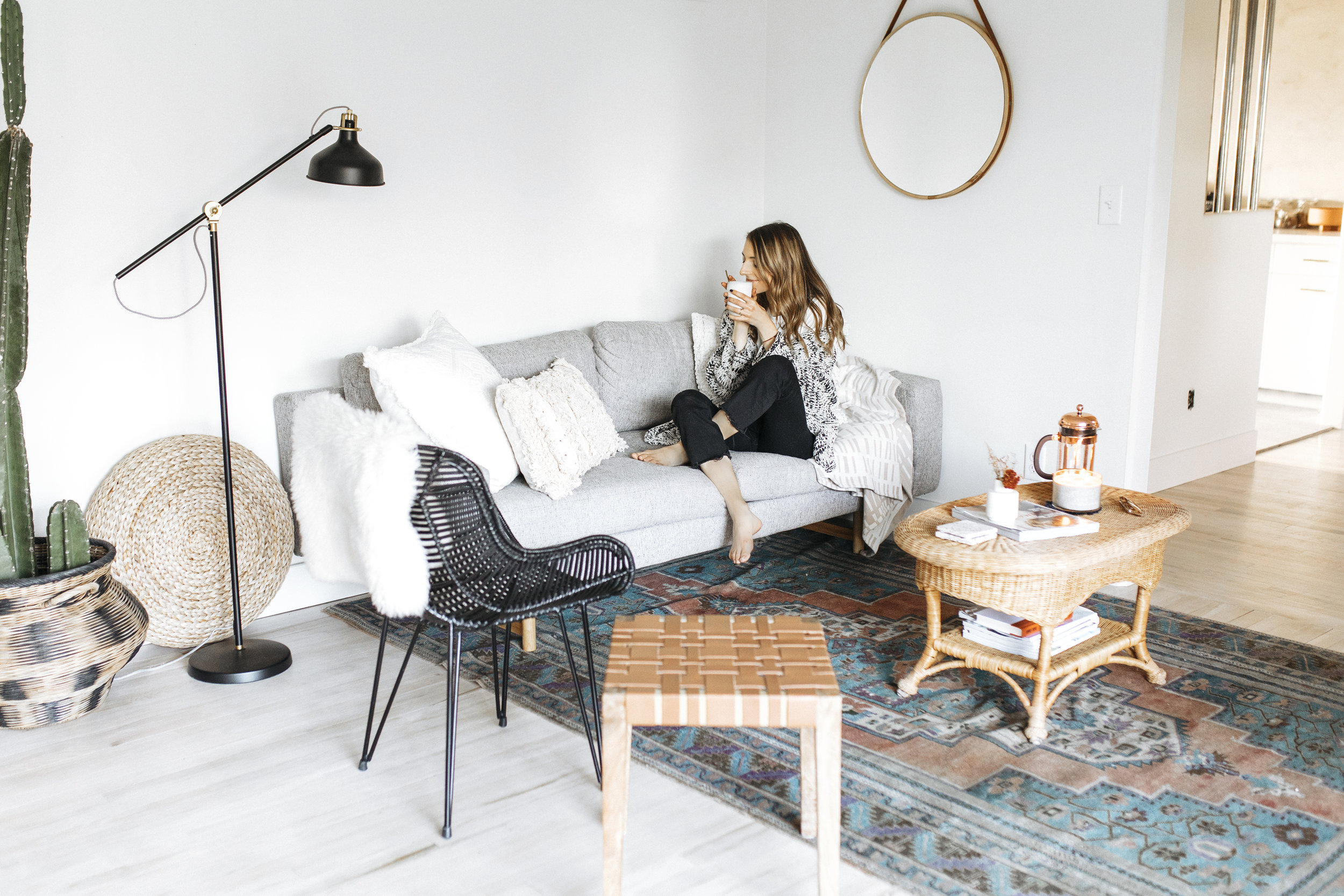 Blogger cuddles with her woven blankets, sipping tea, after hygge -ing up her home for the fall season. Sweaters and candles are in!