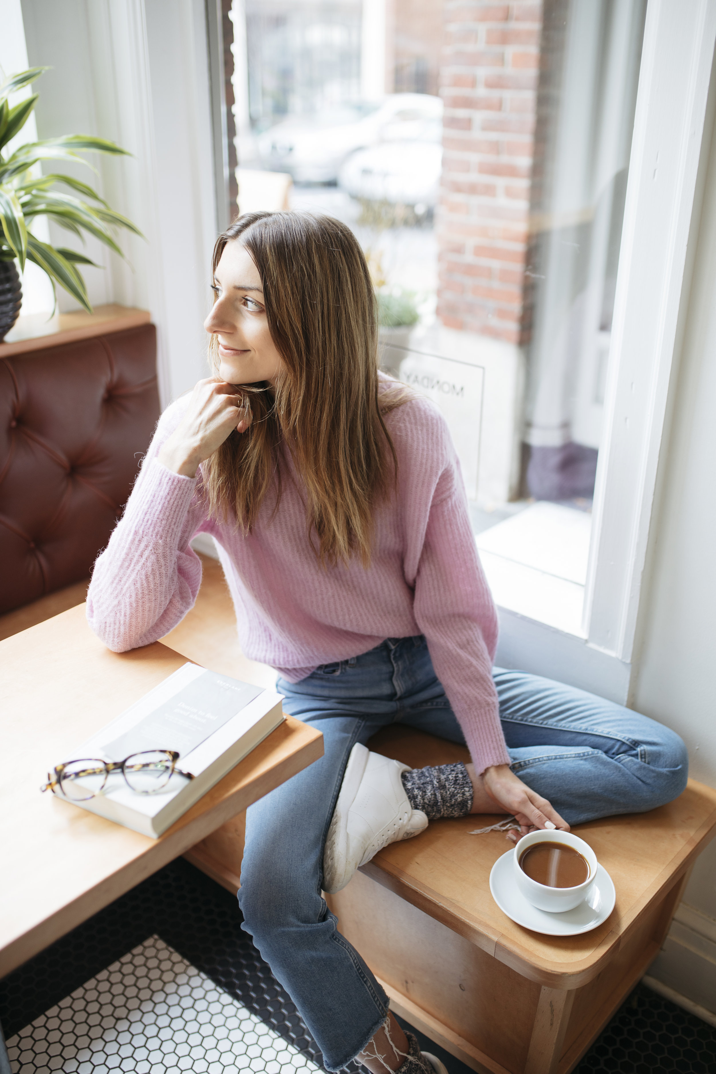 Wearing an ethically made pink sweater, Emily drinks coffee and writes about how to be a better ethical shopper. Read this blog for ethical shopping tips for Black Friday