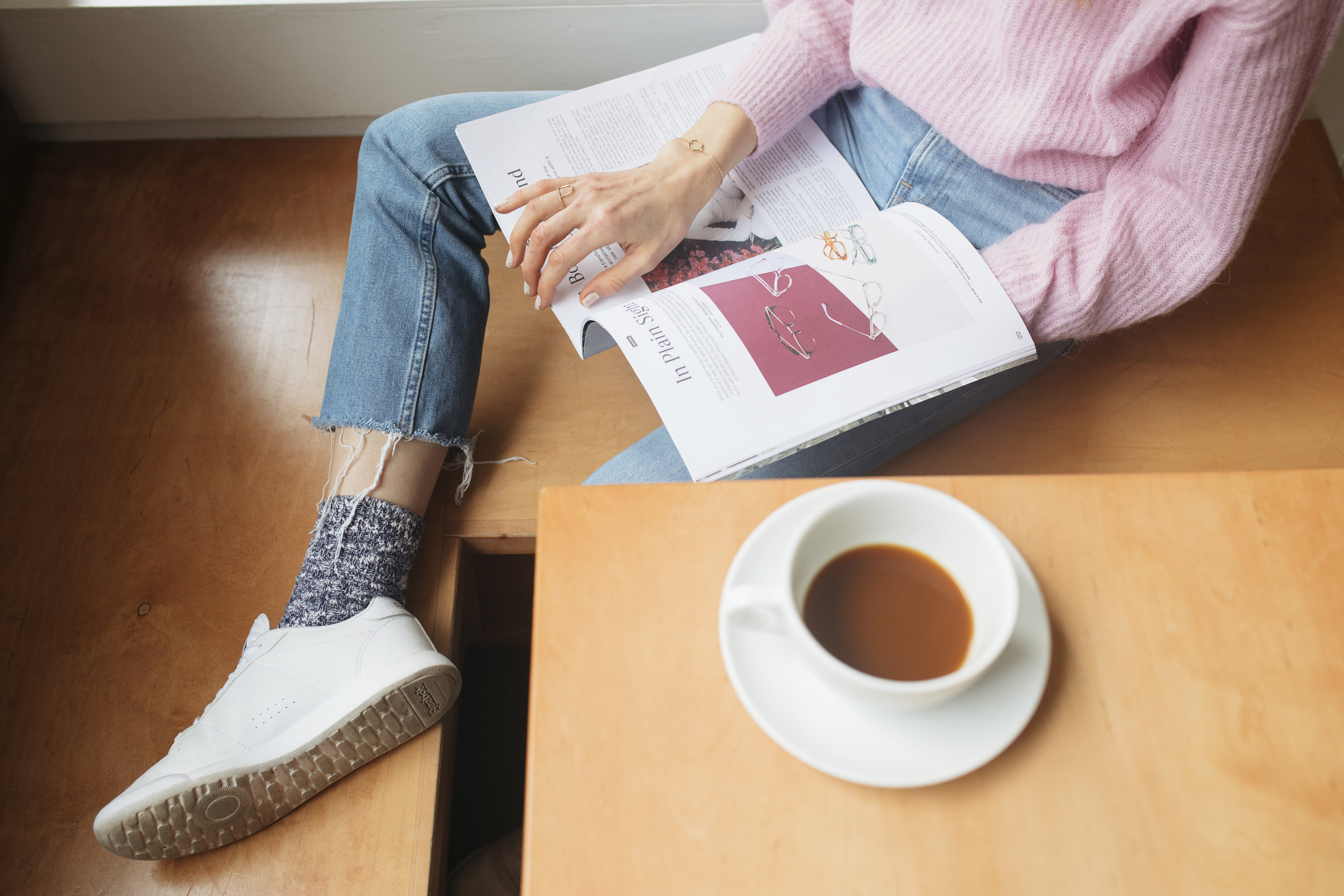 Studying fashion and drinking coffee in a pink ethically made Everlane sweater