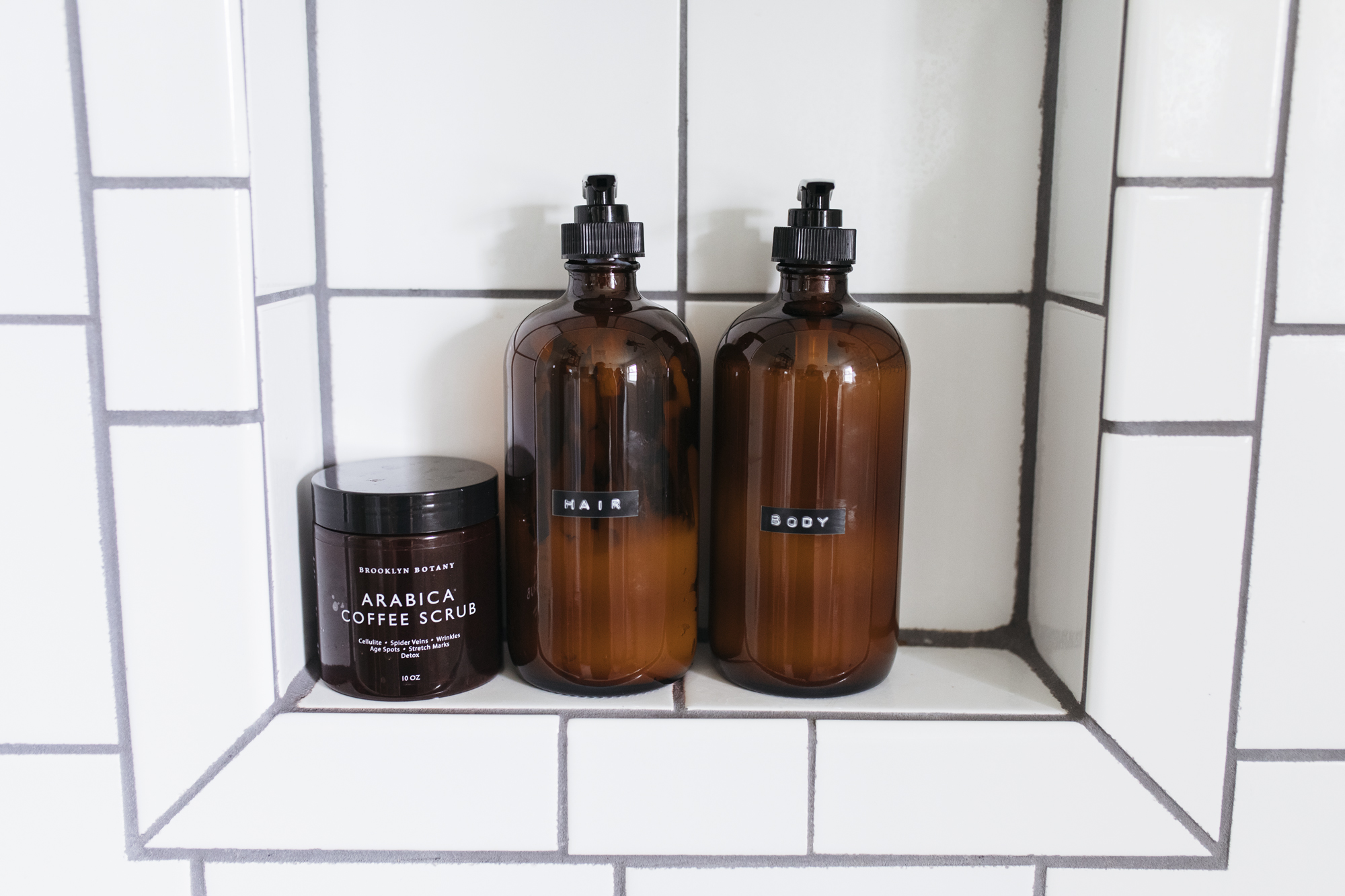 transfer generic shampoo and body wash into pretty  amber glass pump bottles . This creative diy ups your bathroom aesthetic and looks simple.