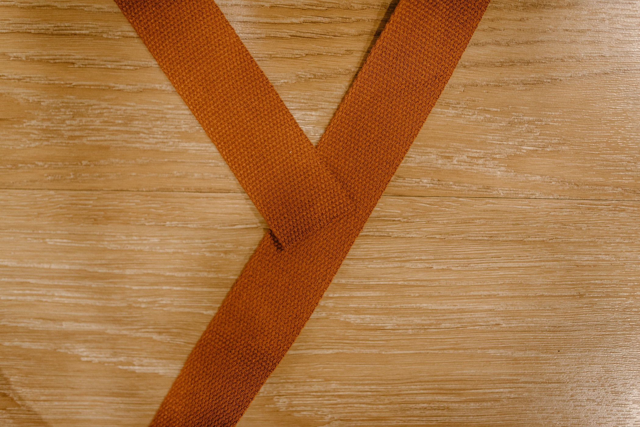"[ place the end of the ribbon in the centre of what will be the ""X"" once the other end is attached ]"