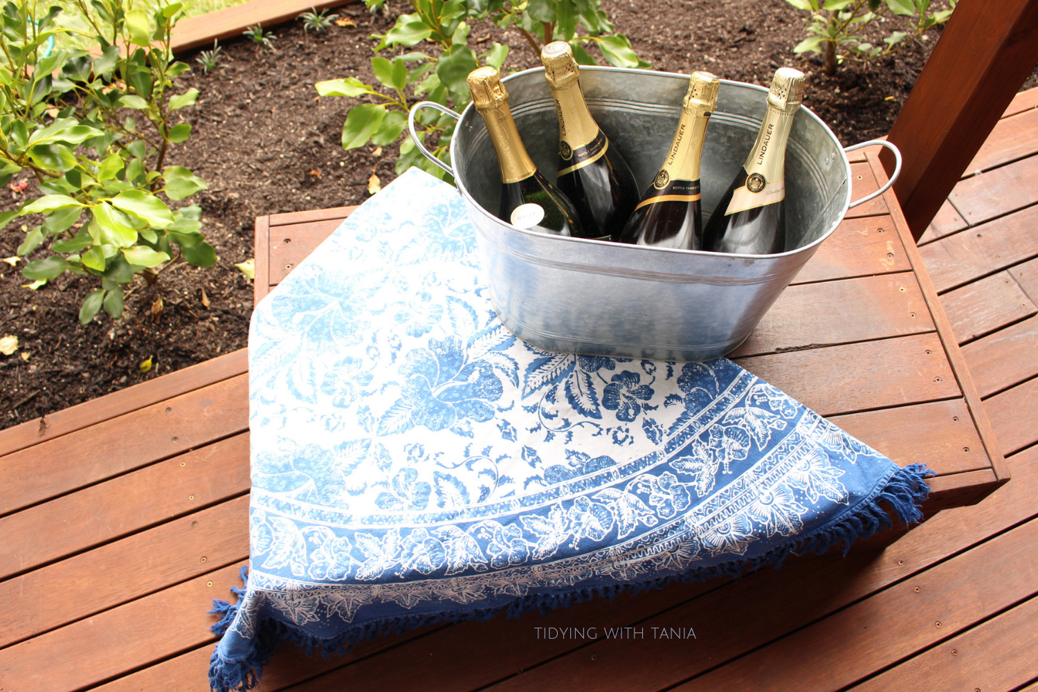 Bottles of sparkling wine in tin bucket outside party.png