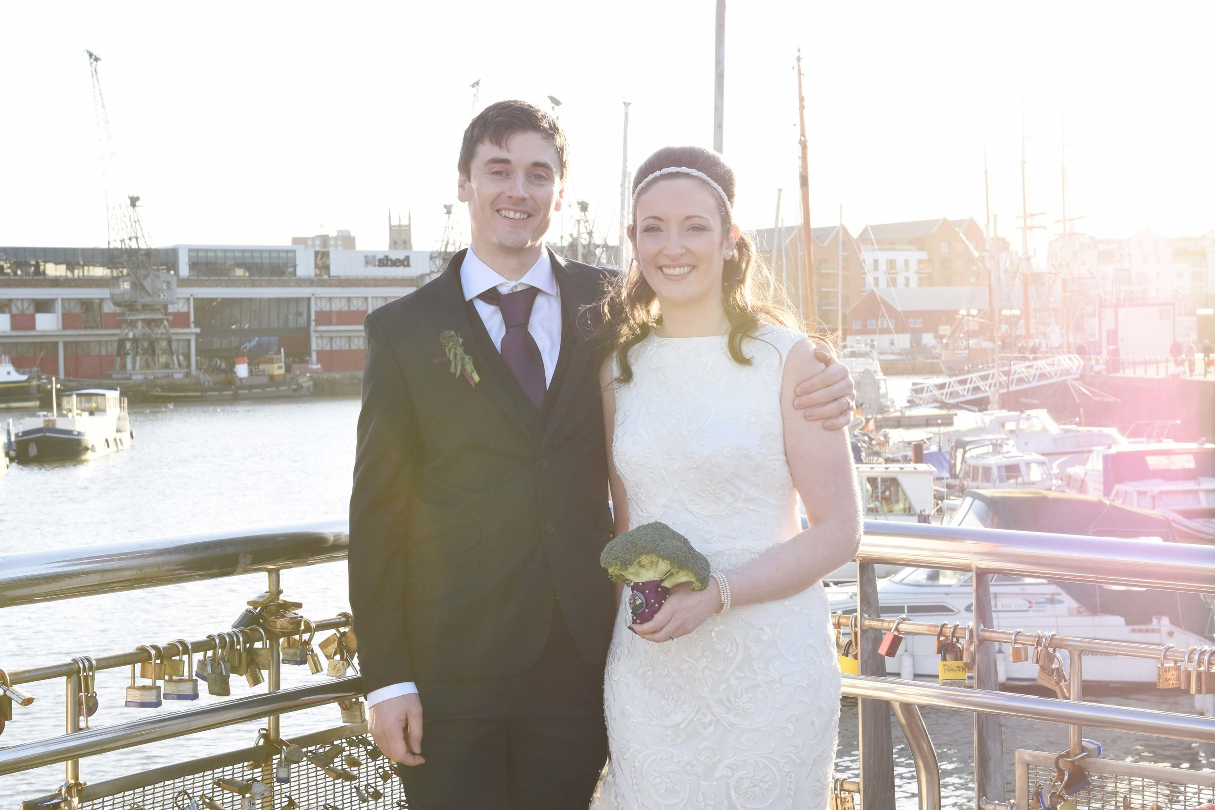 couple standing on the bridge at the water front