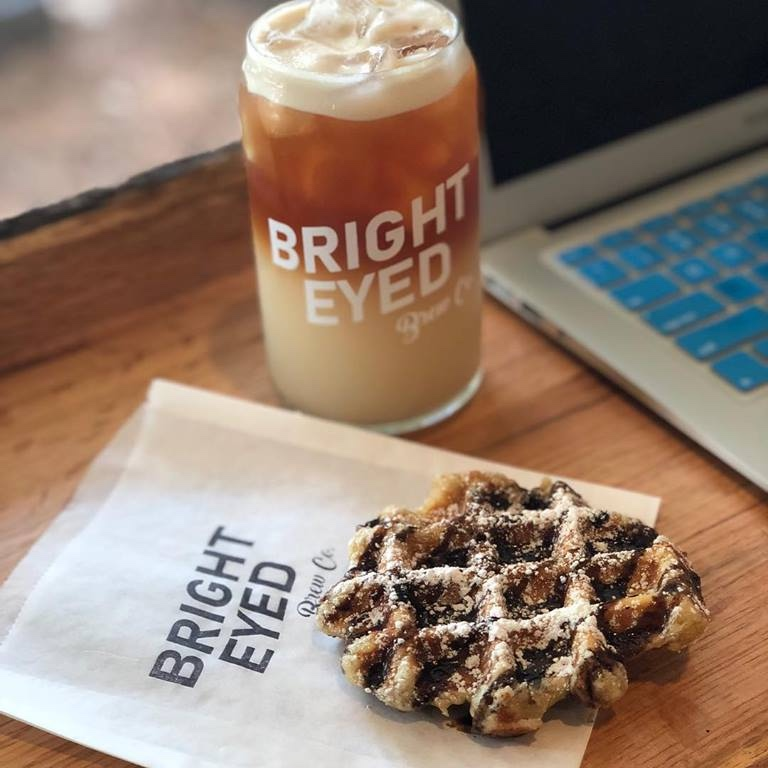 Bright-Eyed Brew Co. - 623 Washington Ave. Ocean Springs, MS 39564Bright-Eyed Brew Co. is known as THE place to get nitro-brew and cold brew coffee on the MS Gulf Coast! They also serve specialty Belgian waffles! Owned and operated by a charming husband and wife team, Bright-Eyed is sure to lift your spirits! Pictured here is an iced chai-chatty and a liege waffle with dark chocolate and powdered sugar. Also, make sure to catch them at the Ocean Springs Fresh Market every Saturday morning!