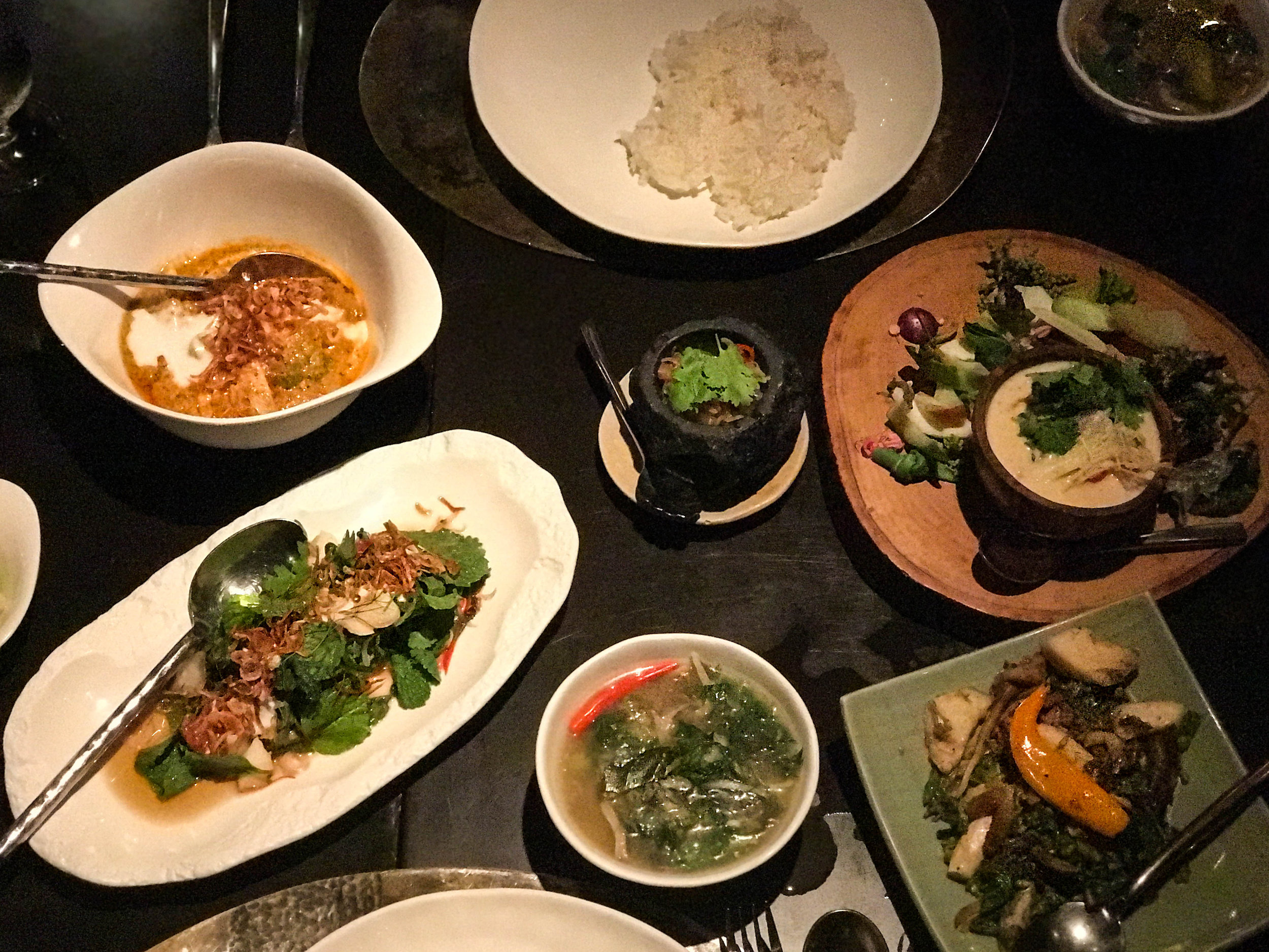"""Main course(s) featuring """"Gapek"""" local water bamboo stir-fried with chili, holy basil and young peppercorns, curry of local greens with Ajat, spicy relish, and Issan vegetable soup."""
