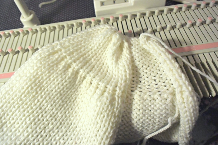 Draw the yarn through the live stitches on the needles. Ready for next step: sewing the side seam.