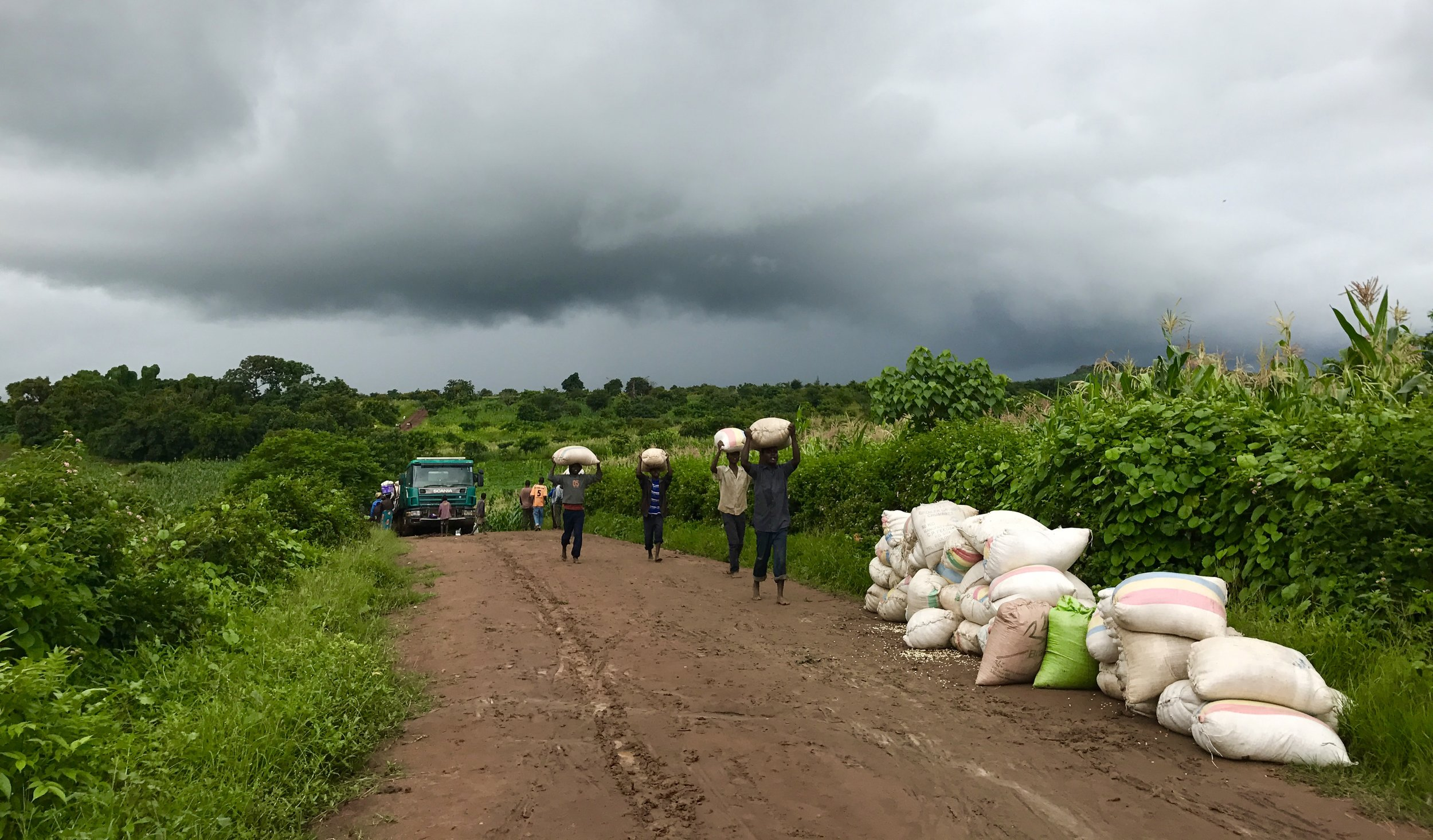 Our van was stuck on the road at this point, roughly 2km from our destination because a grain truck was stuck in the mud halfway up the hill. These men from the village came to help unload all the maize from the truck so it could be pulled up the hill with ropes.