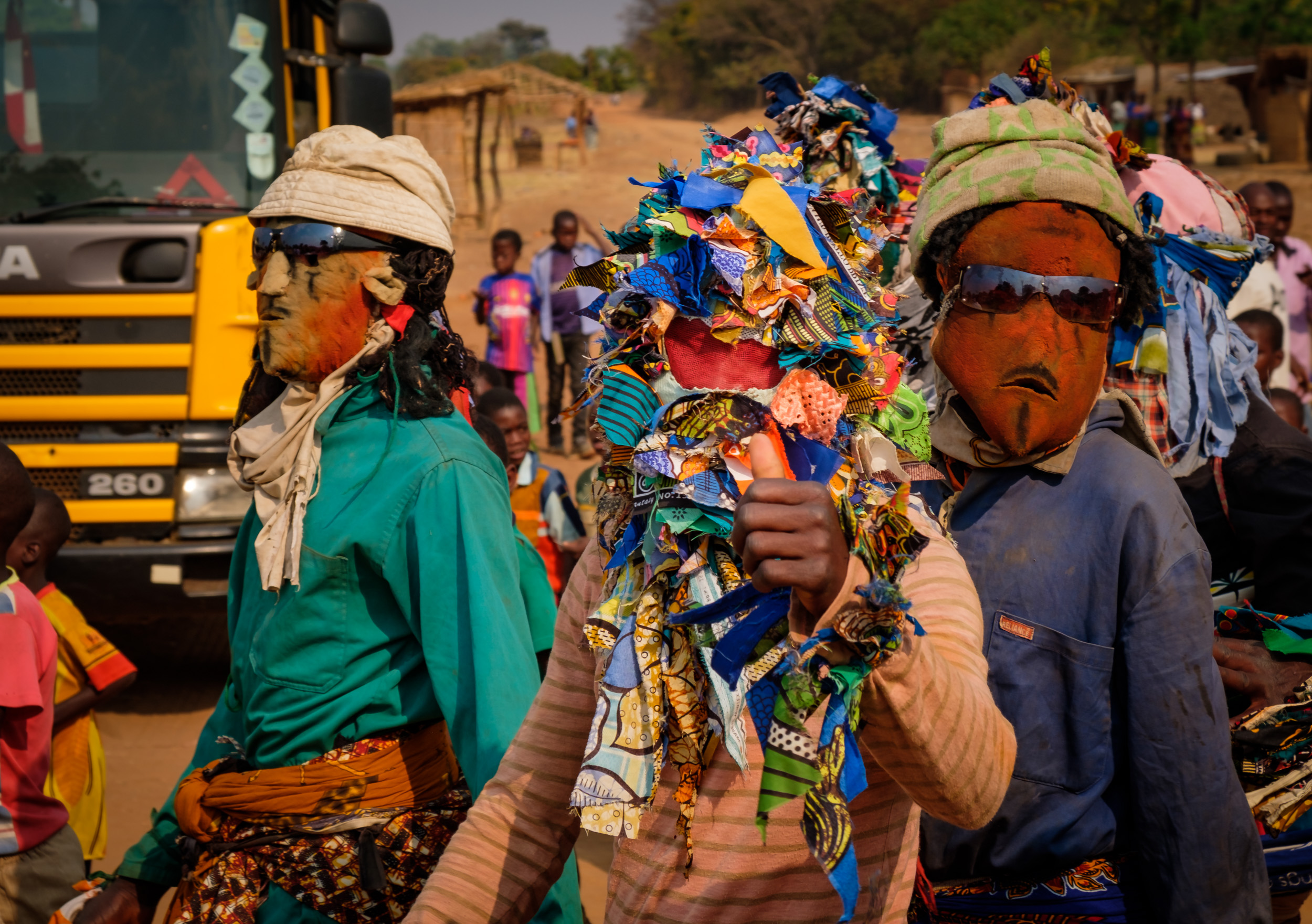 he dancers with their masks walked with the crowd to the house of the new chief before parading to the event.