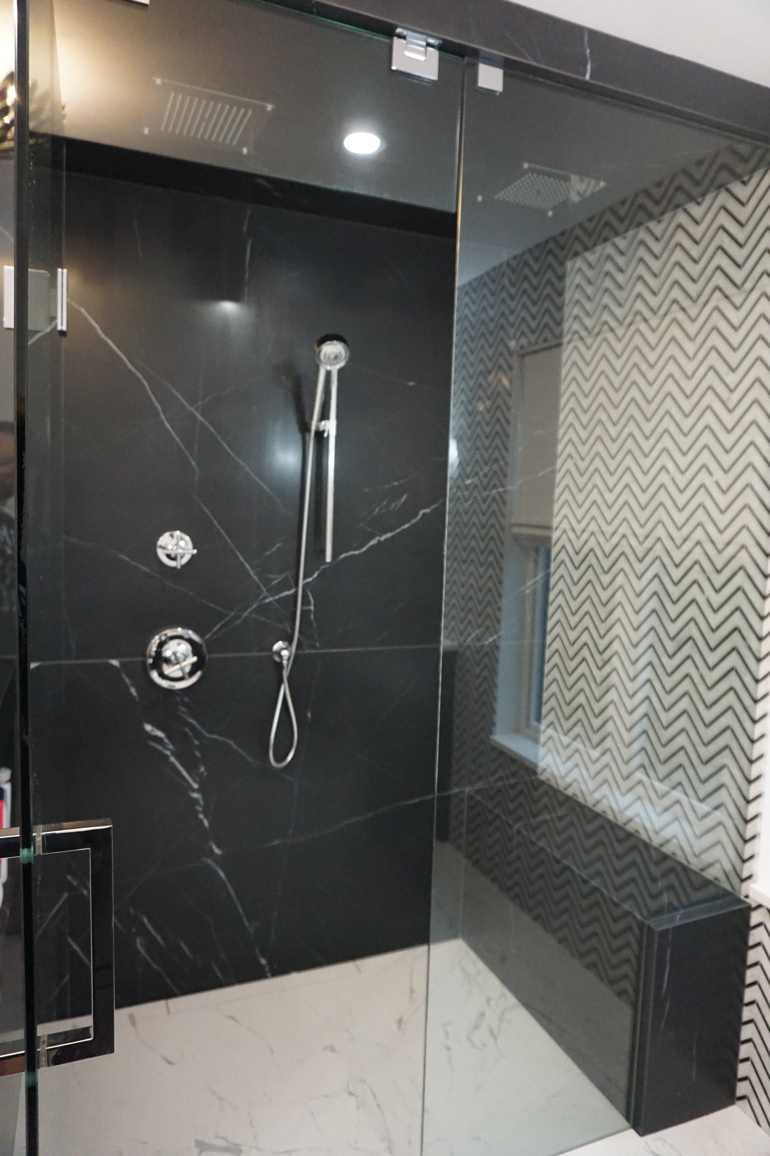 Nero Marquina - This is a honed porcelain Nero marquina porcelain slab, installed in this curb less shower. The bench drop ceiling and pony wall have all been wrapped. With the marble accent wall spilling into the shower space and the bathroom floor flowing seamlessly to the tiled linear drain.
